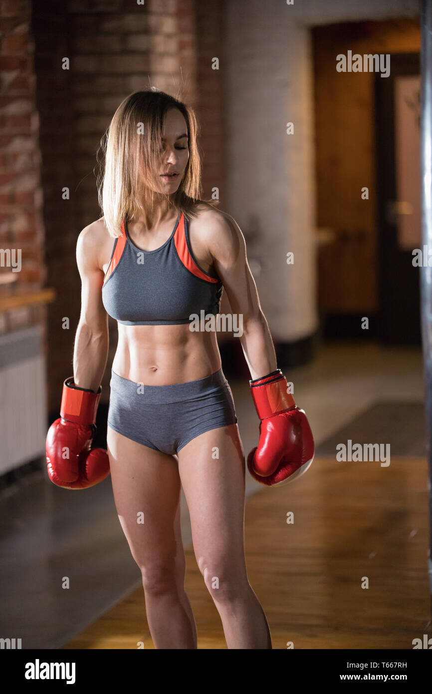 An athletic woman in boxers gloves posing for the camera - Stock Image