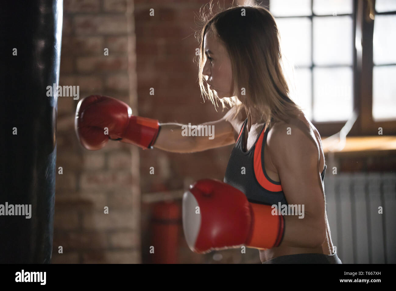 An aggressive woman boxer hitting the punching bag in the gym on the training Stock Photo
