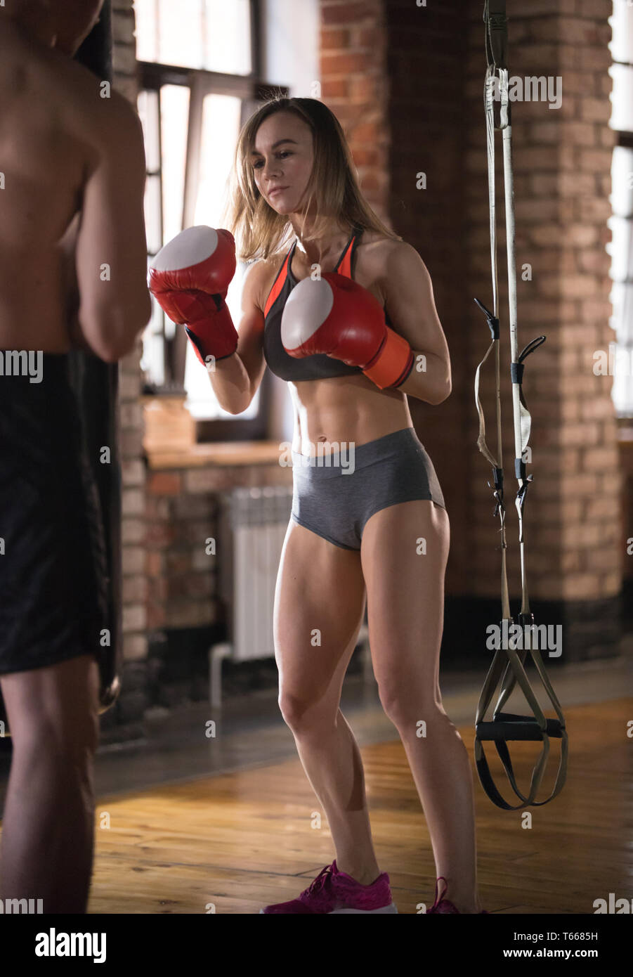 Man and woman in the gym. Trainer holding a punching bag and woman hitting it - Stock Image