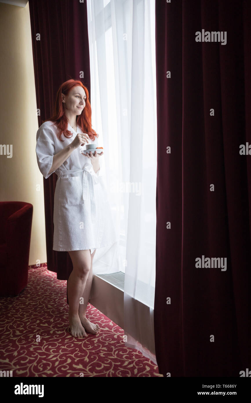 A ginger smiling woman standing by the window and holding a cup of coffee Stock Photo