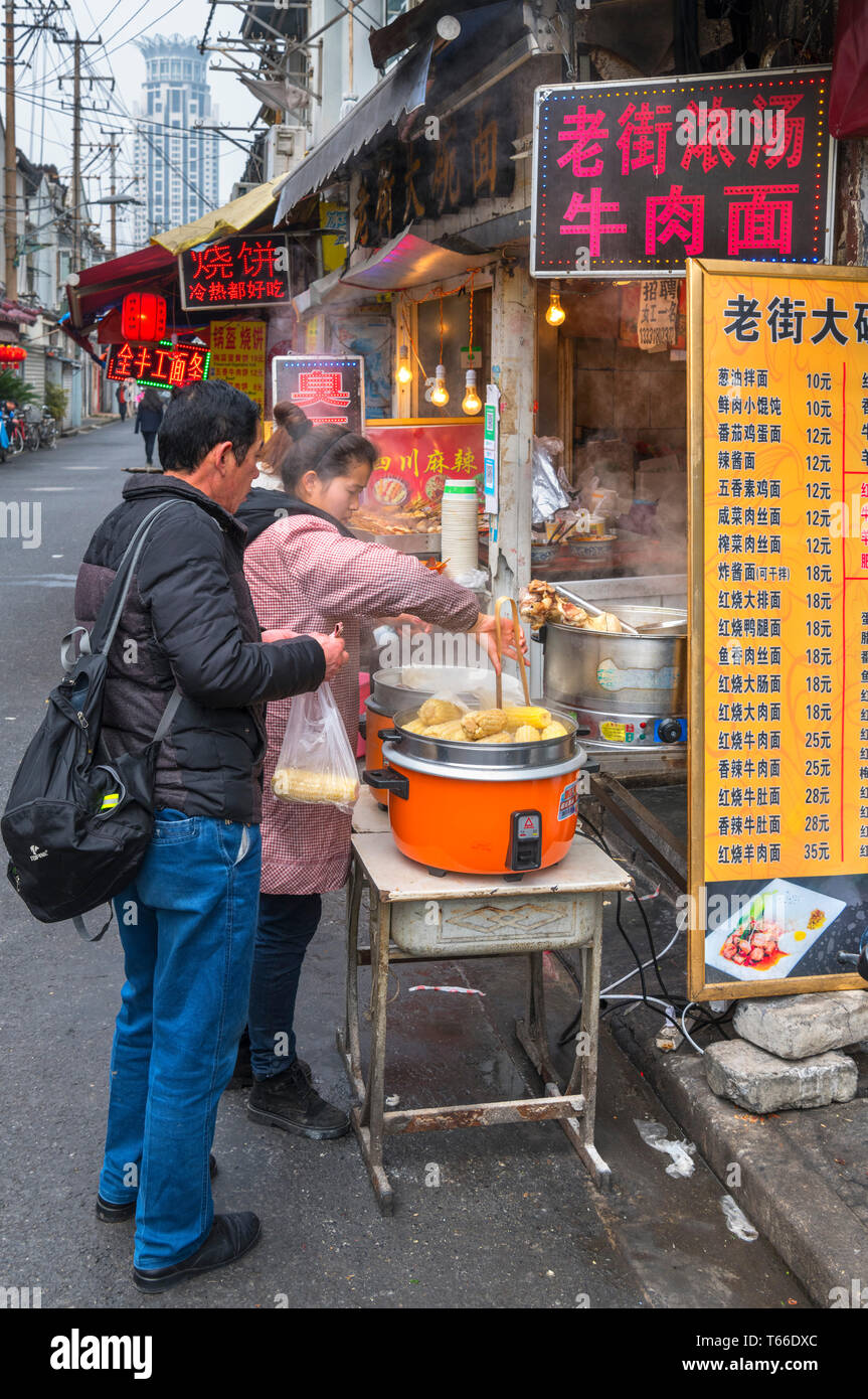 Shanghai, street food. Couple buying food at a traditional food stall in the Old Town (Nanshi district), Shanghai, China - Stock Image