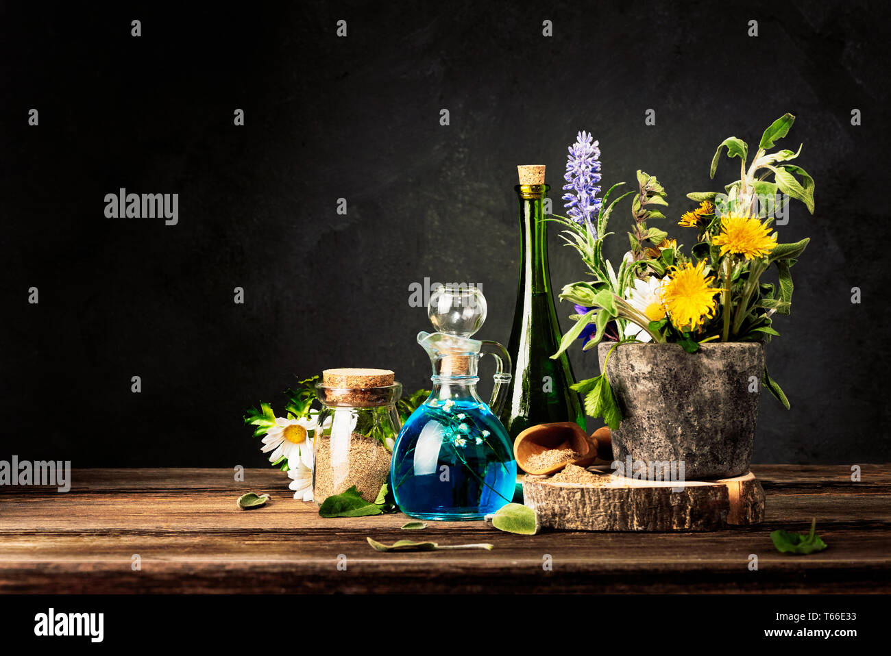 Homeopathy and Alternative Medicine. Healing Herbs in stone mortar and Essential Oil in Glass Bottles. Crushed healing herbs on wooden table. - Stock Image