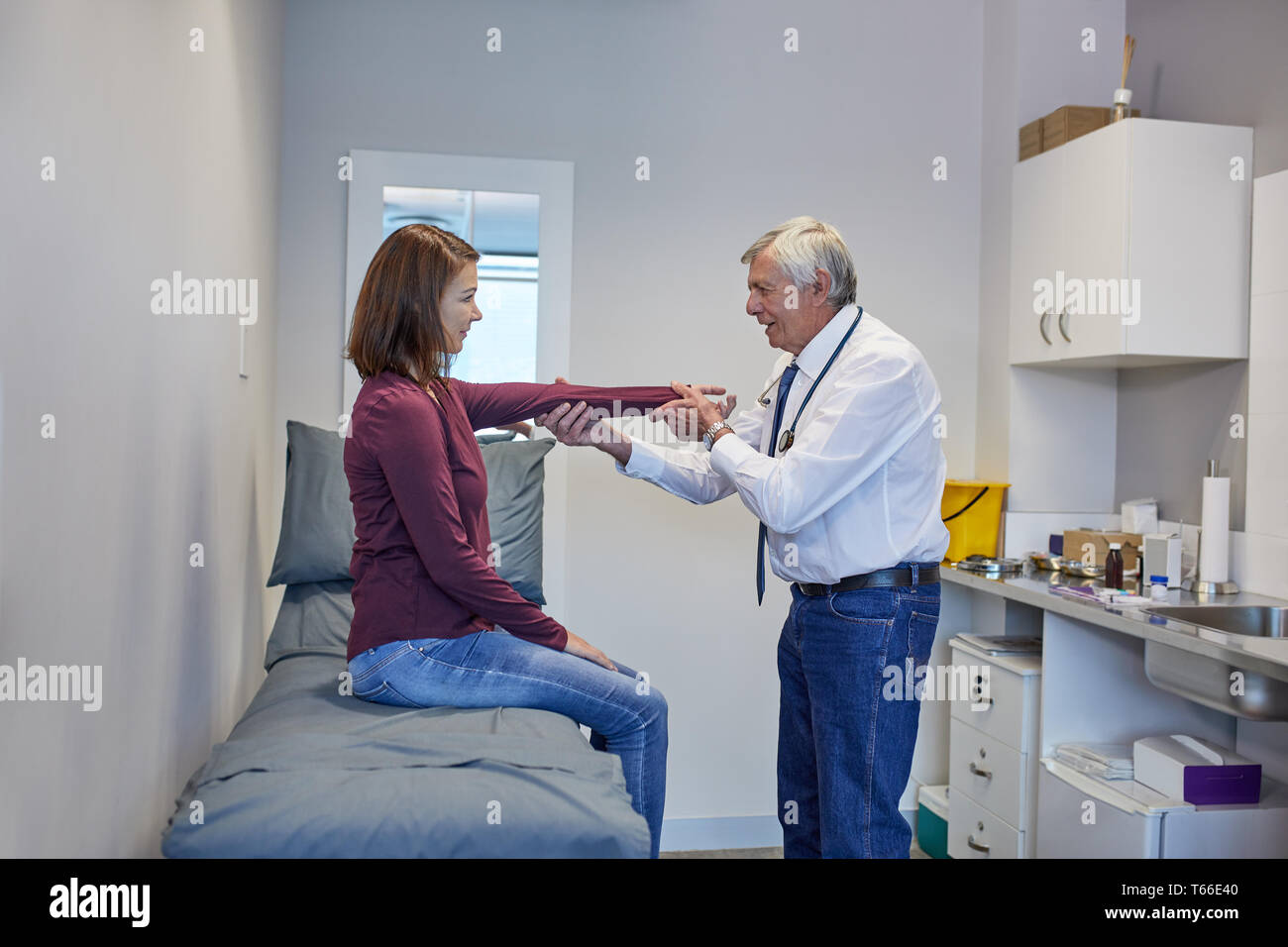 Male doctor examining arm of female patient in clinic examination room Stock Photo