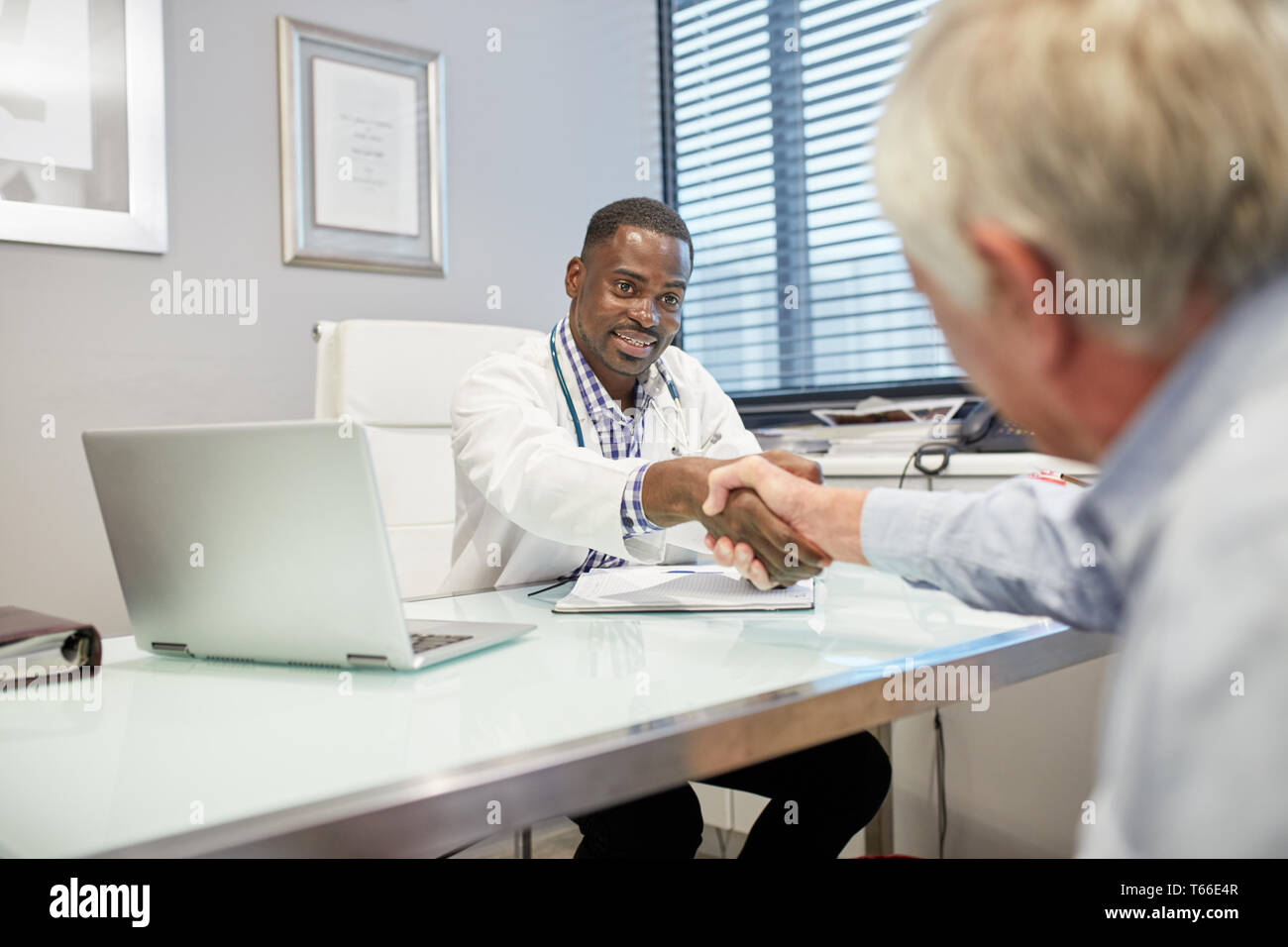 Male doctor shaking hands with senior patient in doctors office Stock Photo