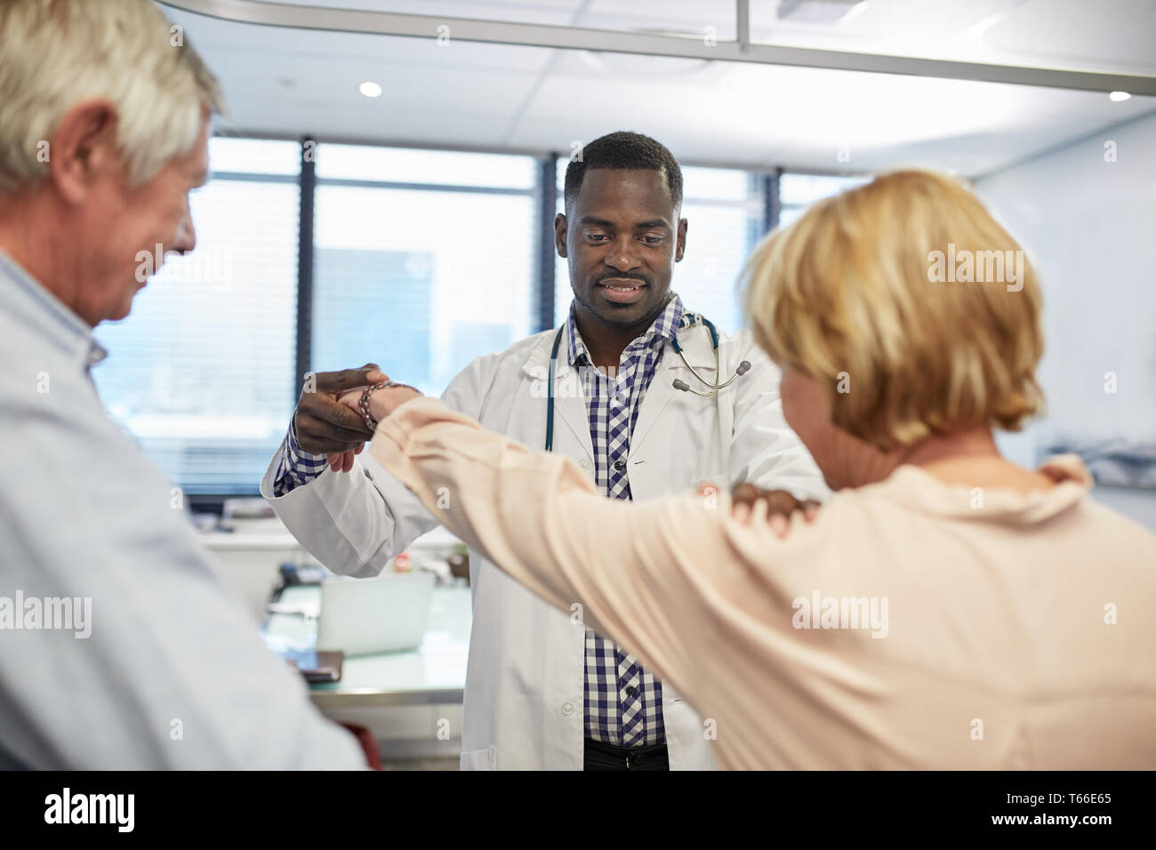 Male doctor examining senior patients shoulder in clinic examination room Stock Photo