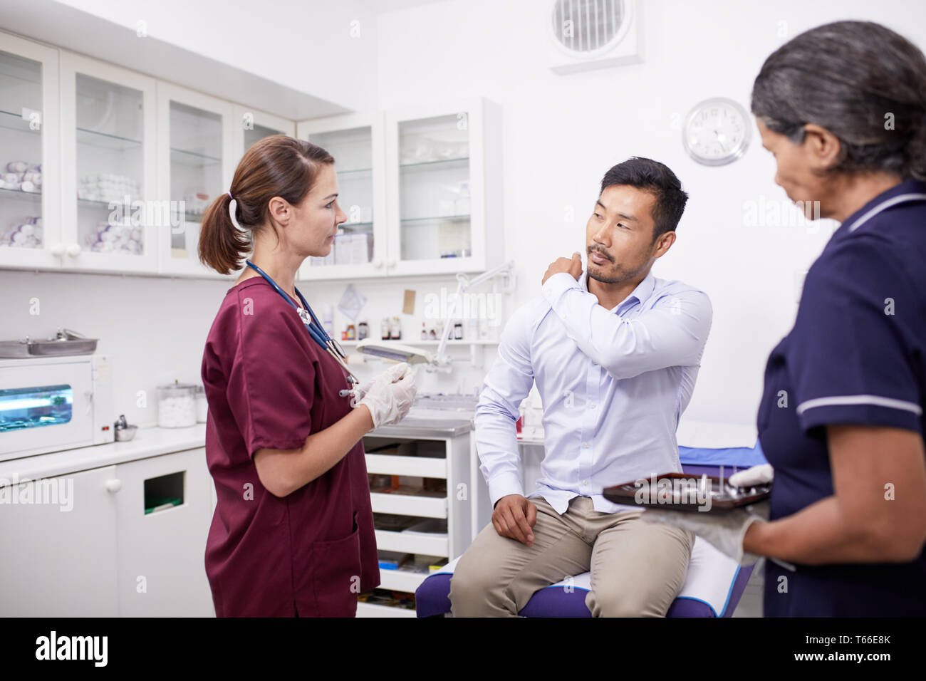 Male patient explaining shoulder pain to female doctor in clinic examination room Stock Photo