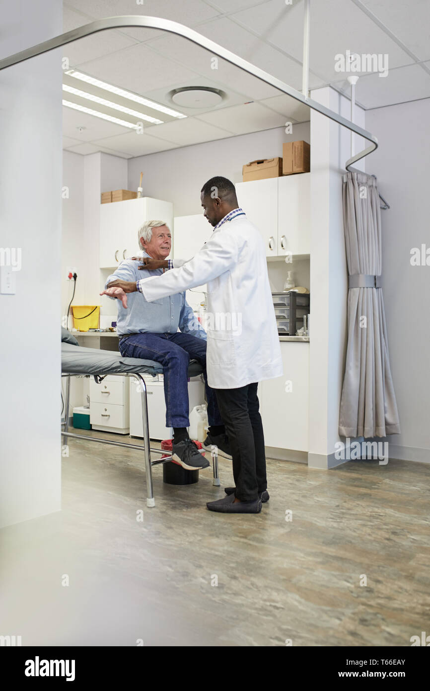 Male doctor examining senior patient in clinic examination room Stock Photo