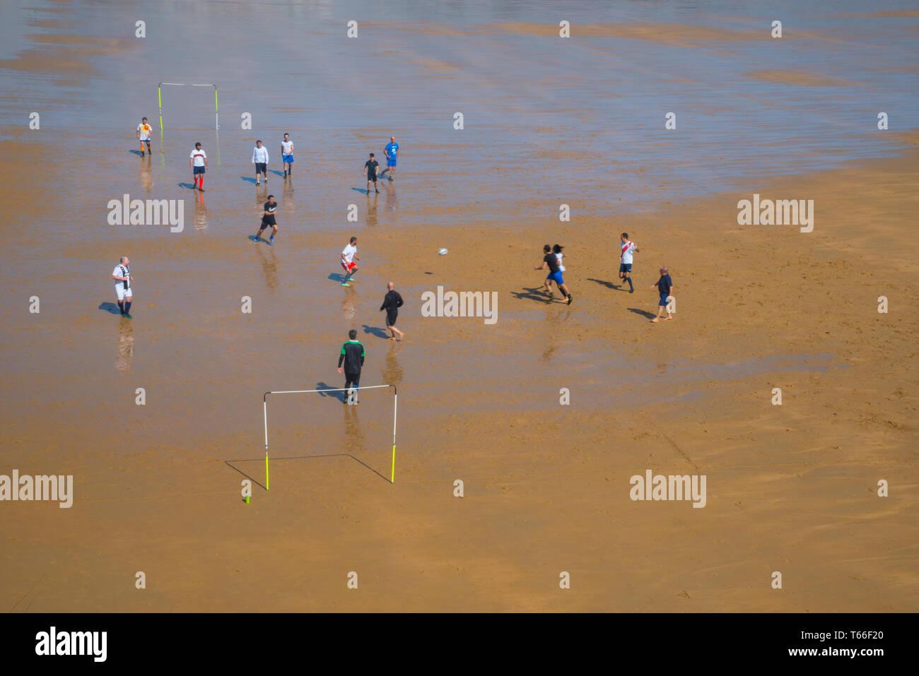 Group of men playing football on wet sand. El Sardinero beach, Santander, Spain. - Stock Image