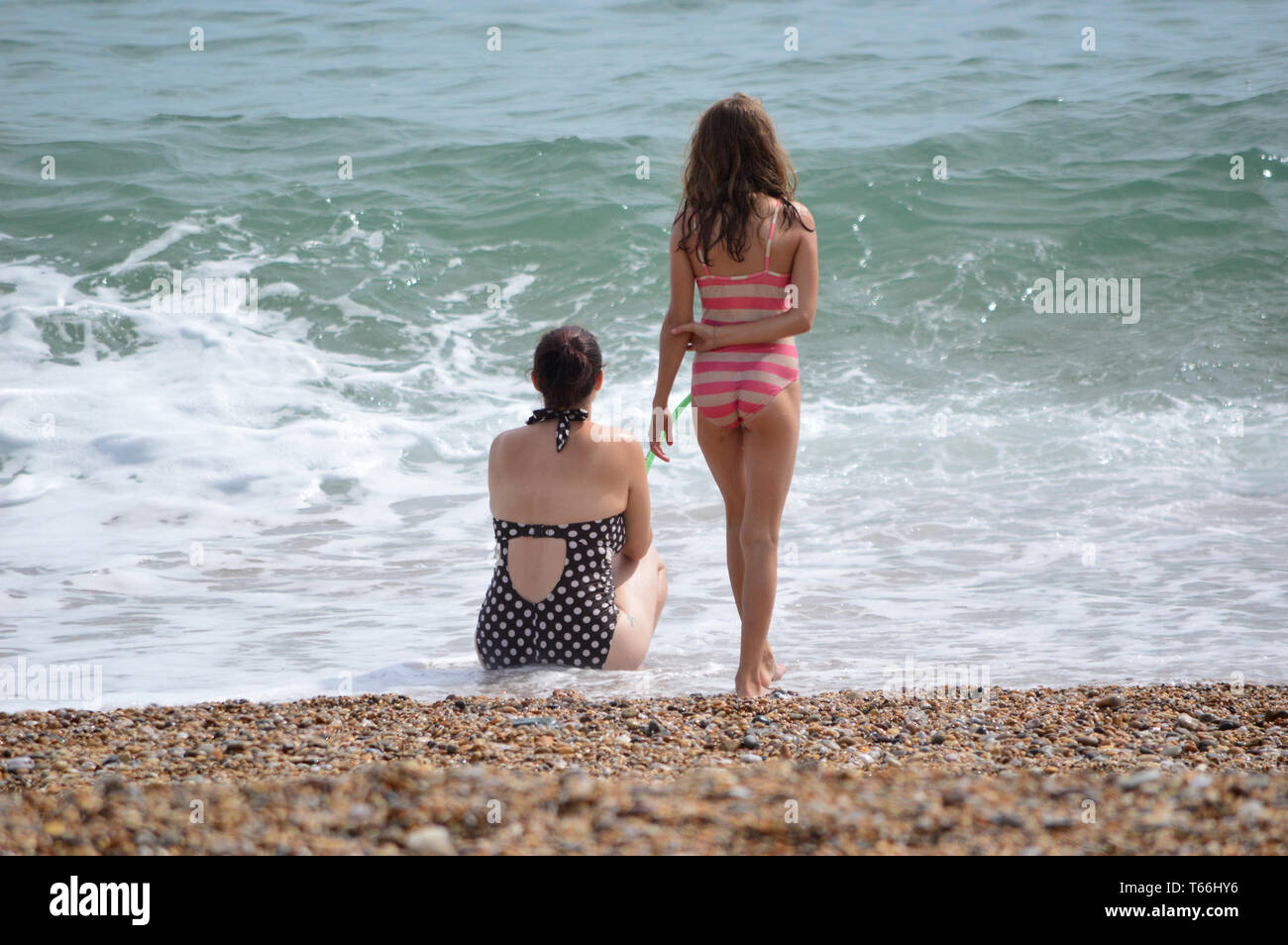 Two young girls in bathing suits, on seaside beach, looking out onto blue sea and white shore waves - Stock Image