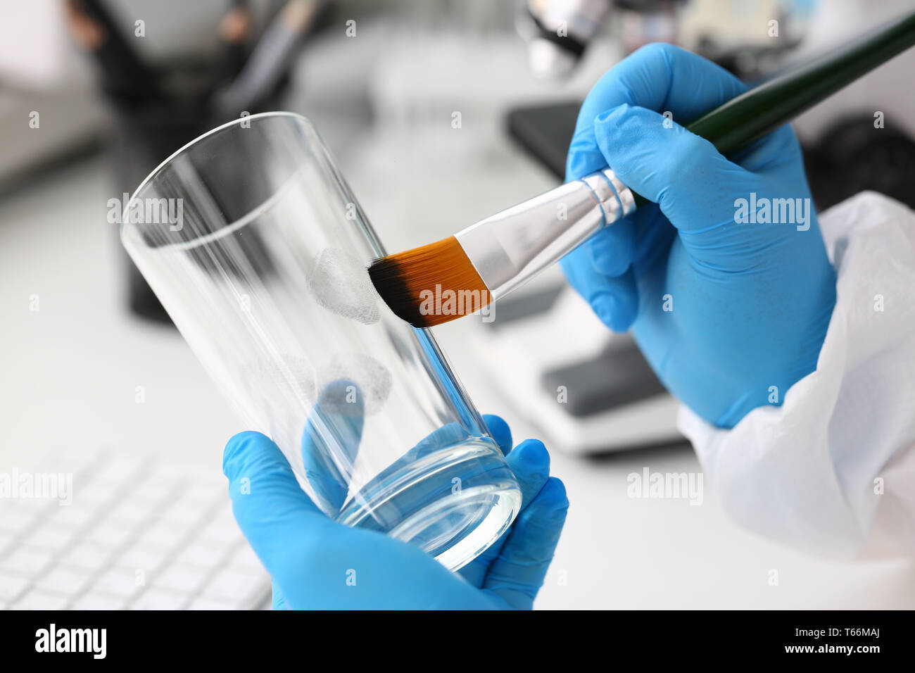 Male hand in blu protective gloves hold brush - Stock Image