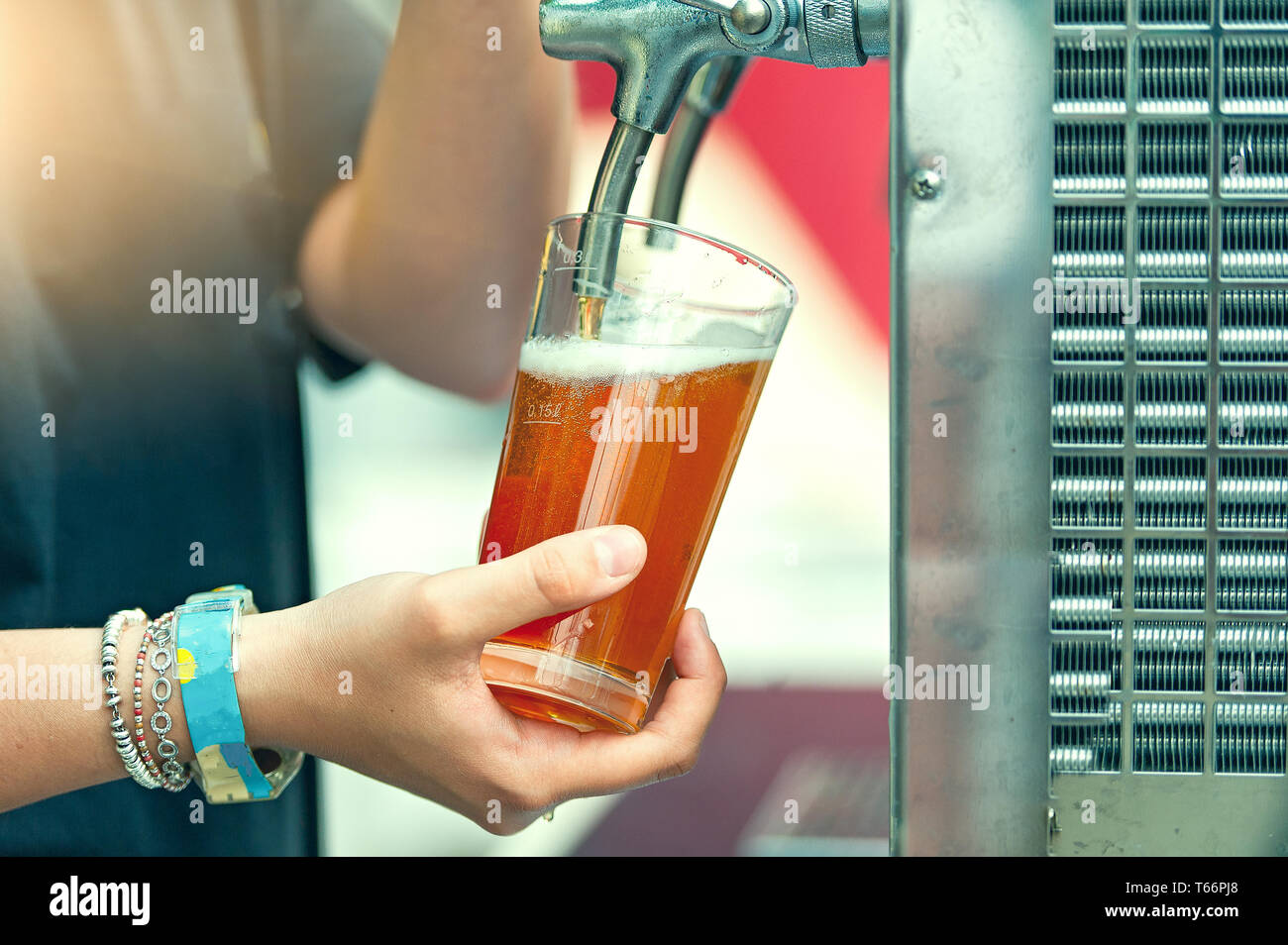 Girl's hand while tapping beer in a platyrus mug at a folk festival - Stock Image