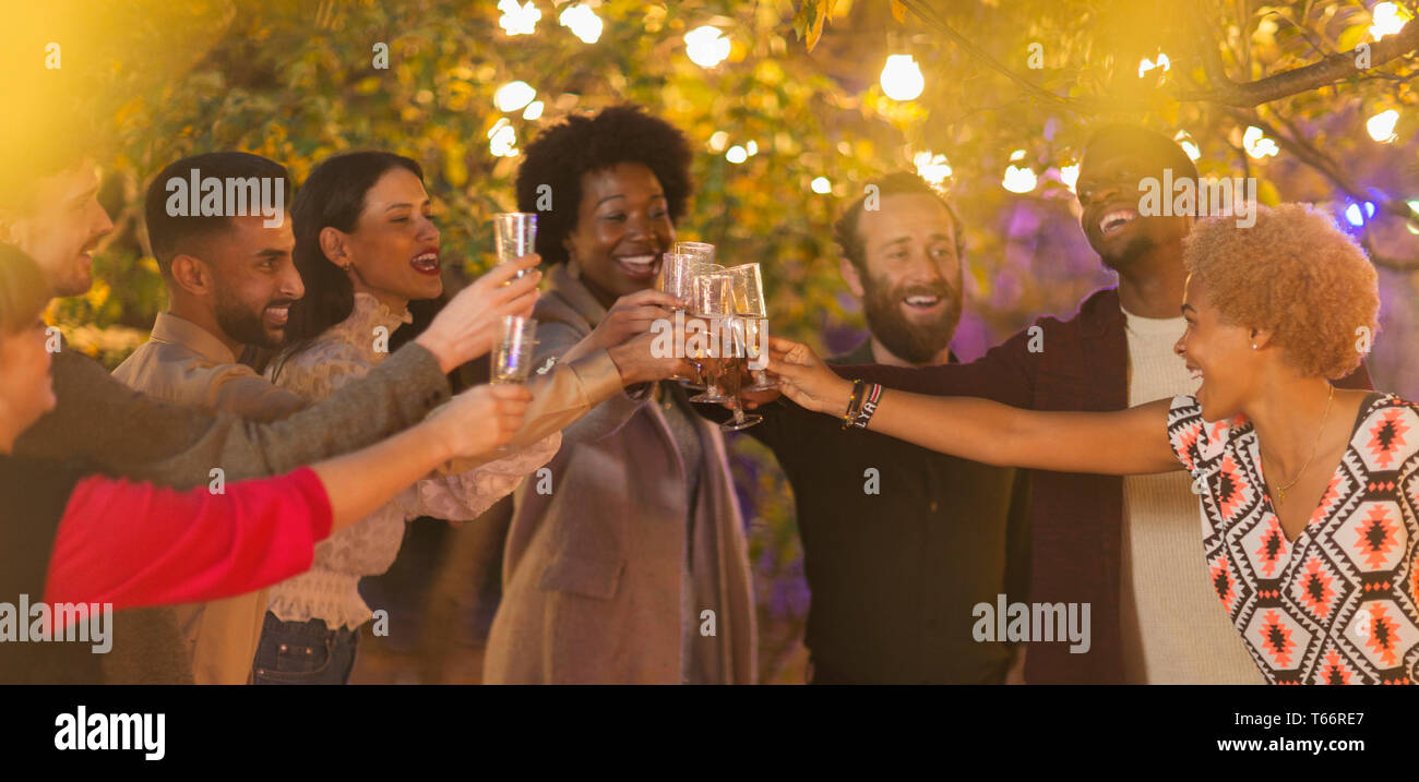 Friends celebrating, toasting champagne at dinner garden party - Stock Image