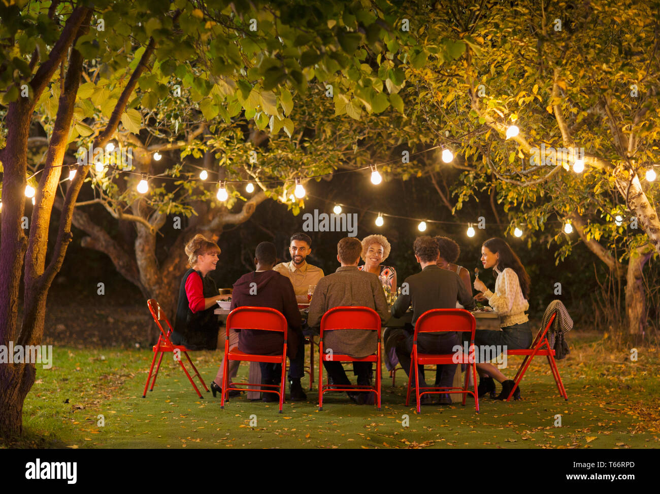 Friends enjoying dinner garden party under trees with fairy lights Stock Photo