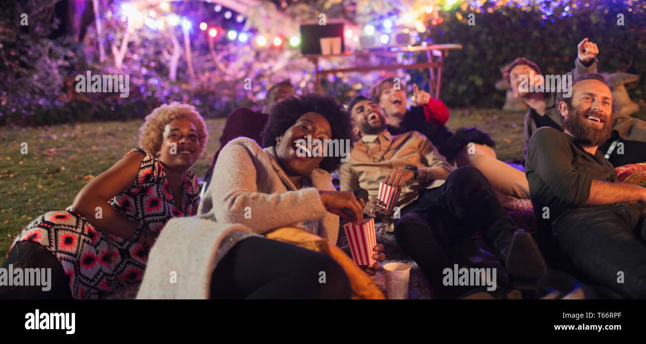 Laughing friends watching movie in backyard - Stock Image