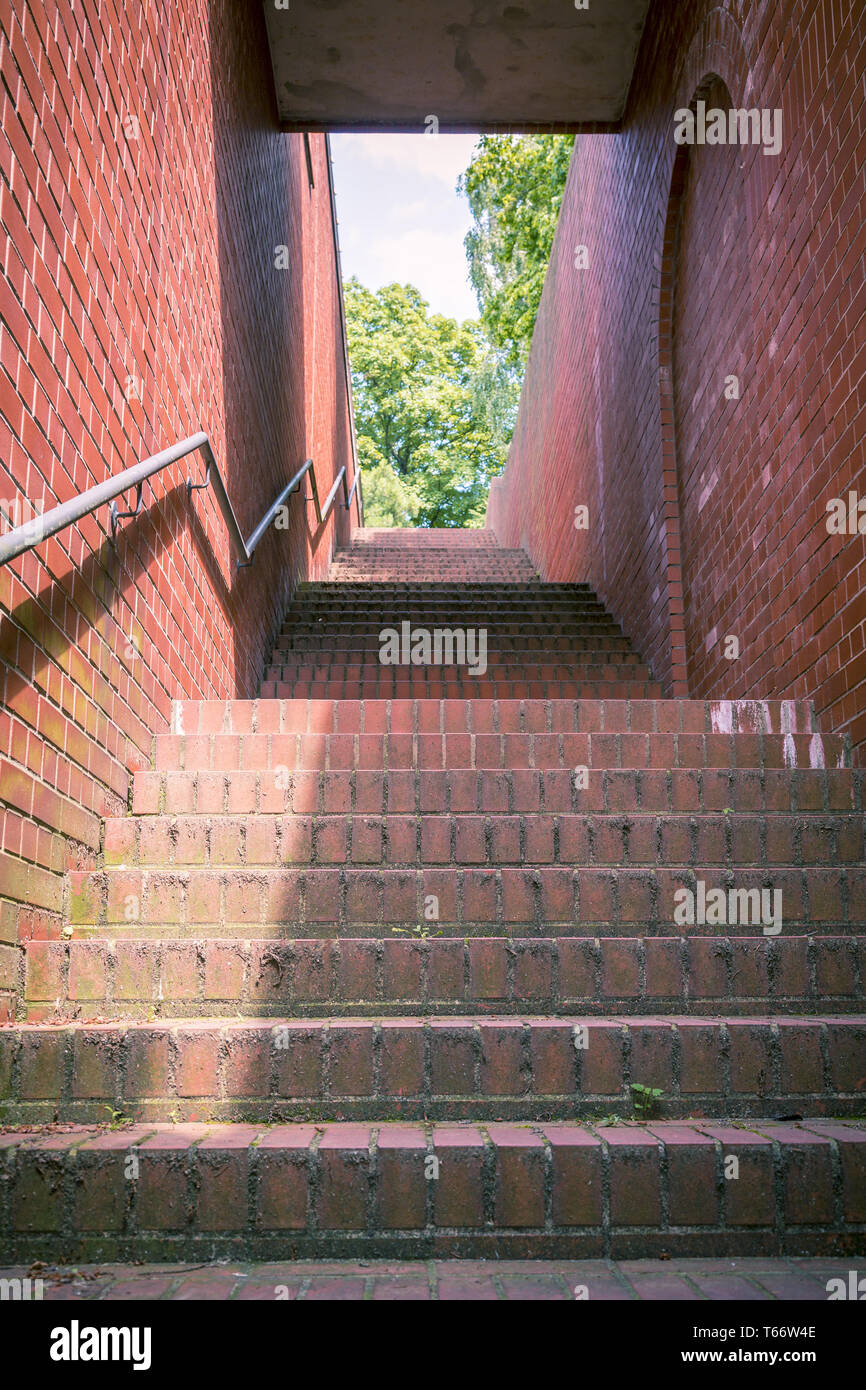 a tunnel like stairway with red bricks and handrail - Stock Image