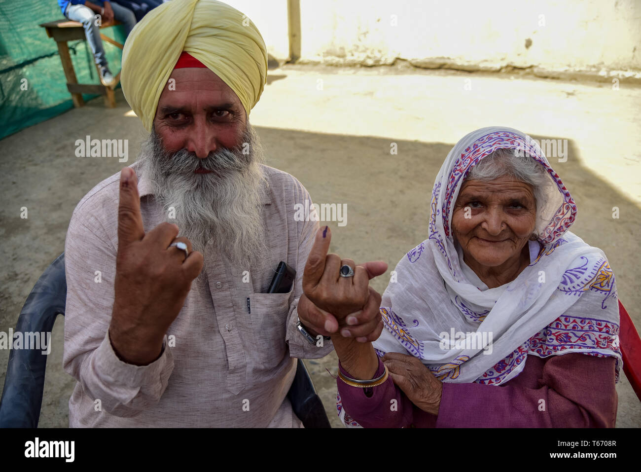 Kashmiri voters are seen showing off their inked fingers after casting their votes outside a polling station in Kulgam, South of Srinagar. On the fourth phase of India's Parliamentary elections, Indians went to polls to cast their ballots amid complete shutdown and internet gag. Stock Photo