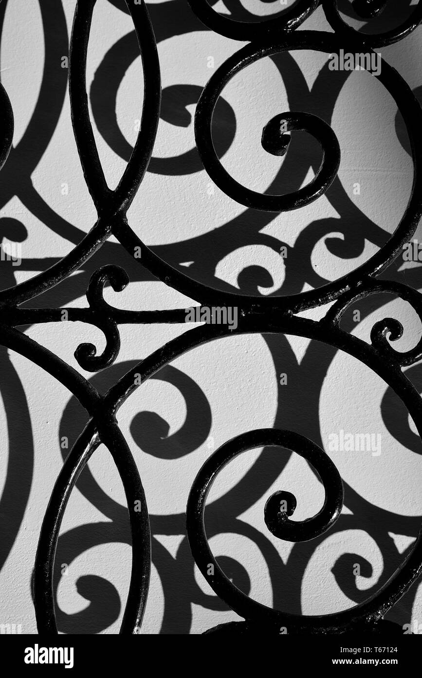 Curved iron bars casting shadows on wall. Stock Photo