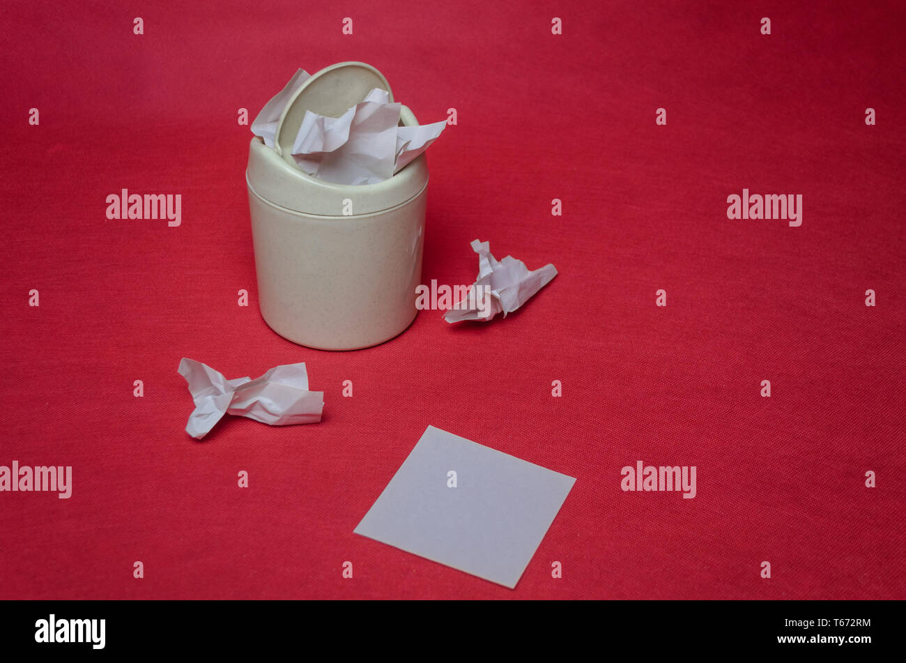Light trash bin on a red background. Closeup of crumpled sheets of paper. The concept of environmental recycling of paper waste. - Stock Image