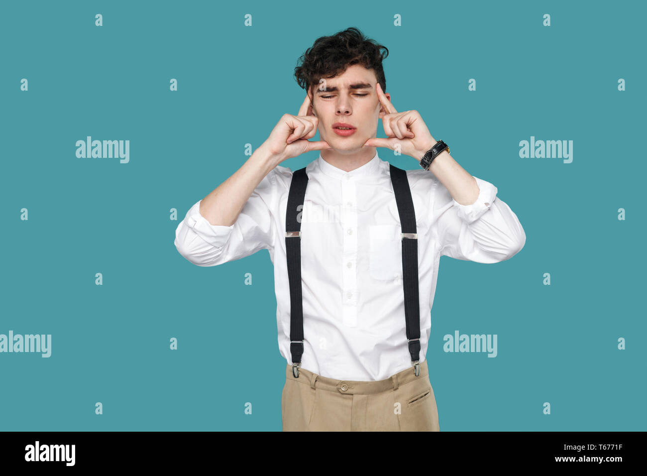 Headache or confusion. upset man holding his head. Portrait of handsome hipster curly young businessman in classic white shirt and suspender standing. Stock Photo