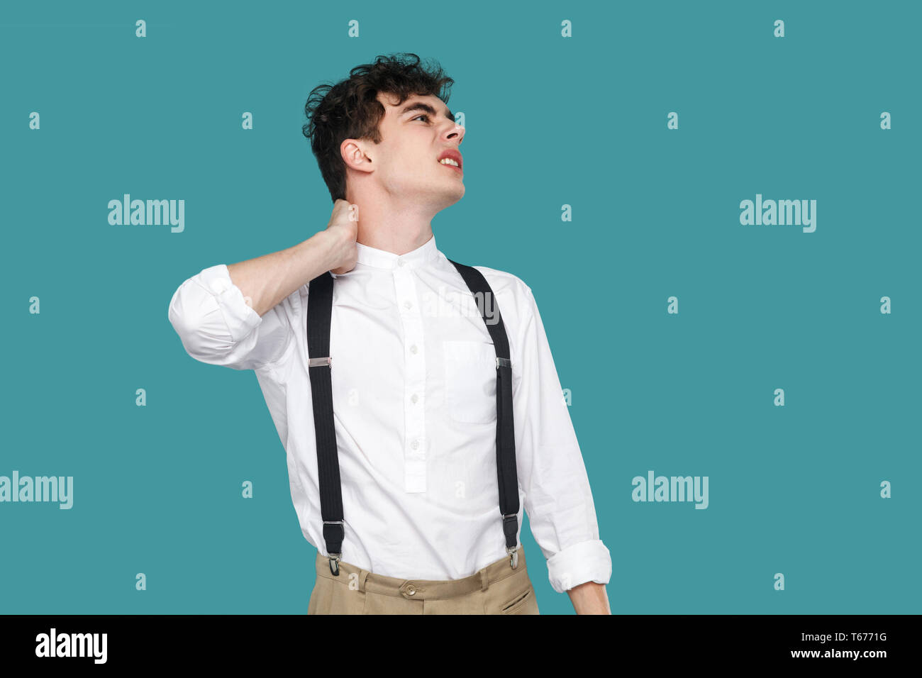 Neck pain. Man holding his painful or injury pain. Portrait of handsome curly young businessman in classic casual white shirt and suspender standing.  - Stock Image