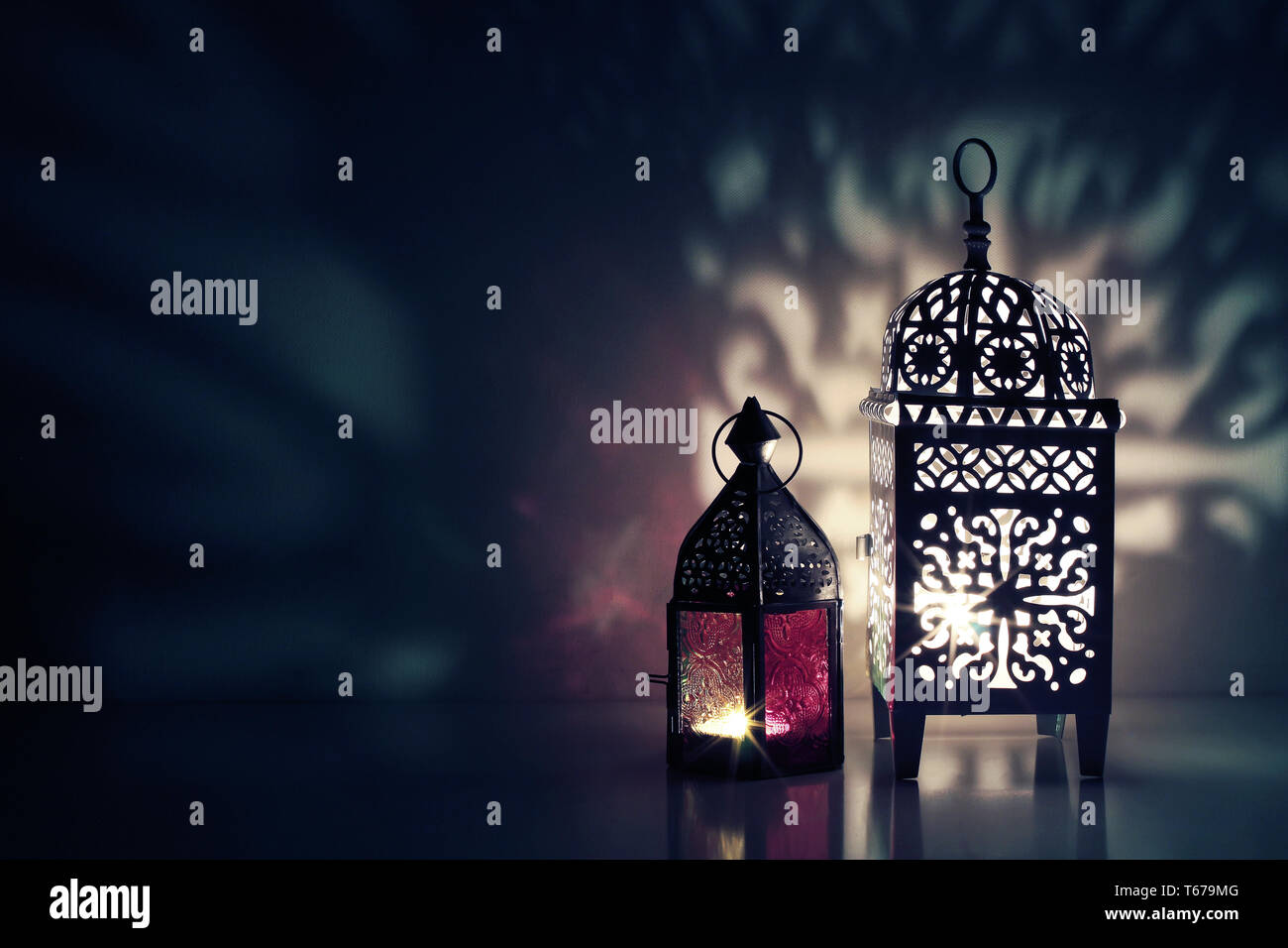 Moroccan ornamental lanterns on the table glowing at night. Greeting card, invitation for Muslim holy month Ramadan Kareem. Festive blue background - Stock Image
