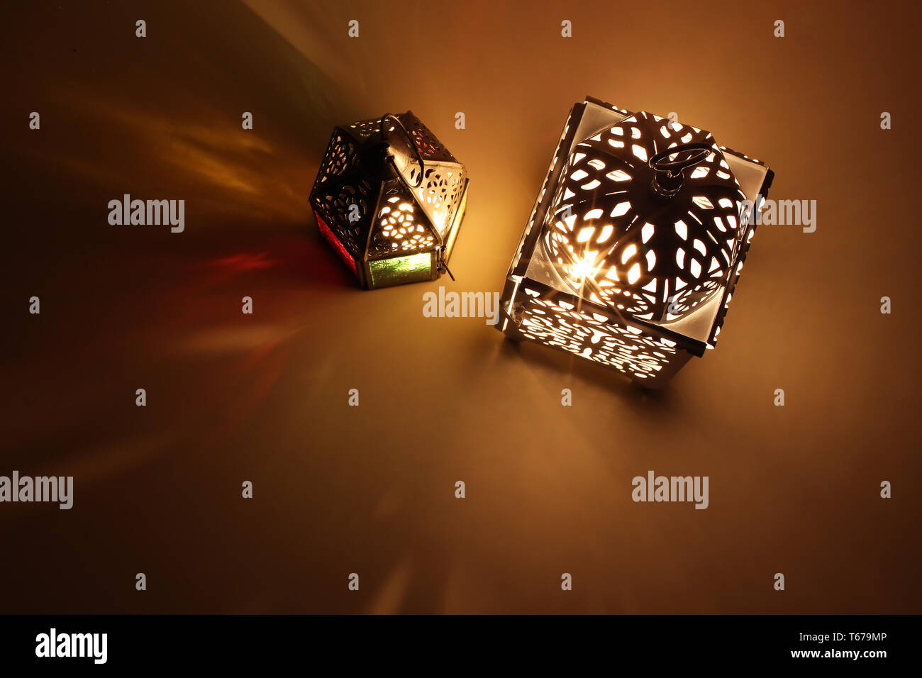 Couple of glowing Moroccan ornamental lanterns on table. Decorative golden shadows. Greeting card, invitation for Muslim holy month Ramadan Kareem - Stock Image