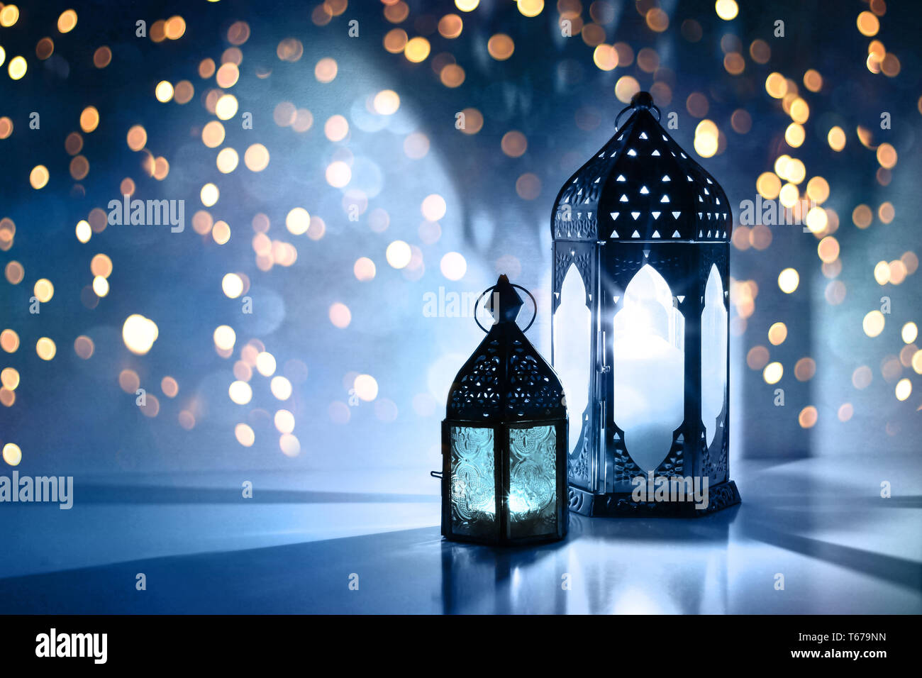 Couple of glowing Moroccan ornamental lanterns on the table. Greeting card, invitation for Muslim holy month Ramadan Kareem. Festive blue night - Stock Image