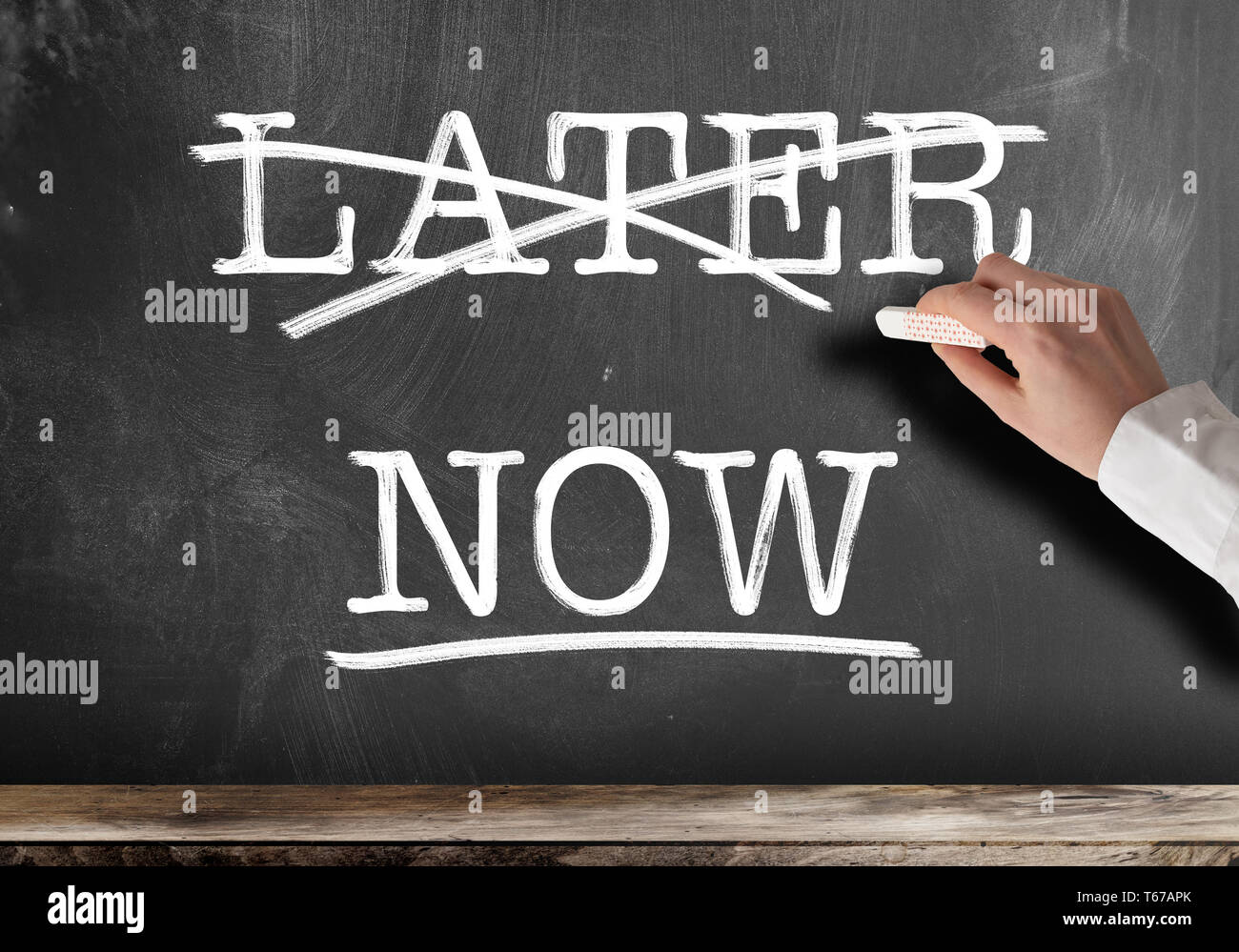 words NOW and LATER written on blackboard with LATER struck out anti procrastination concept - Stock Image