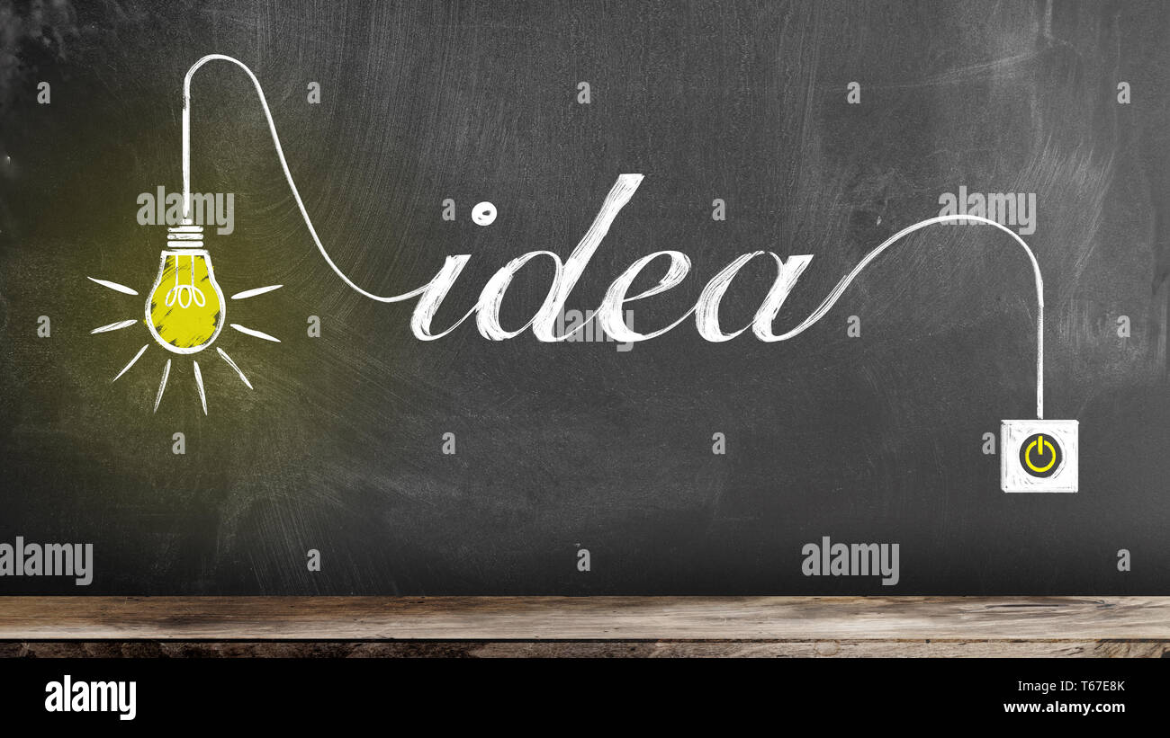 chalk drawing of glowing light bulb and word IDEA on blackboard innovation concept - Stock Image
