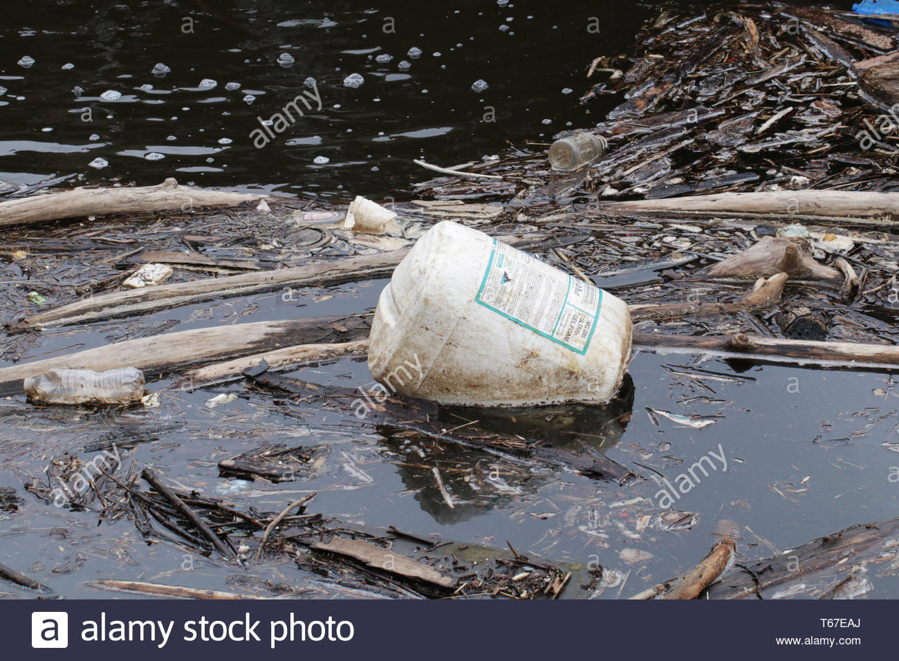 MINNEAPOLIS, MN - APRIL 29 2019: A large plastic jug floats among other plastic pollution and river debris in the Mississippi River. - Stock Image