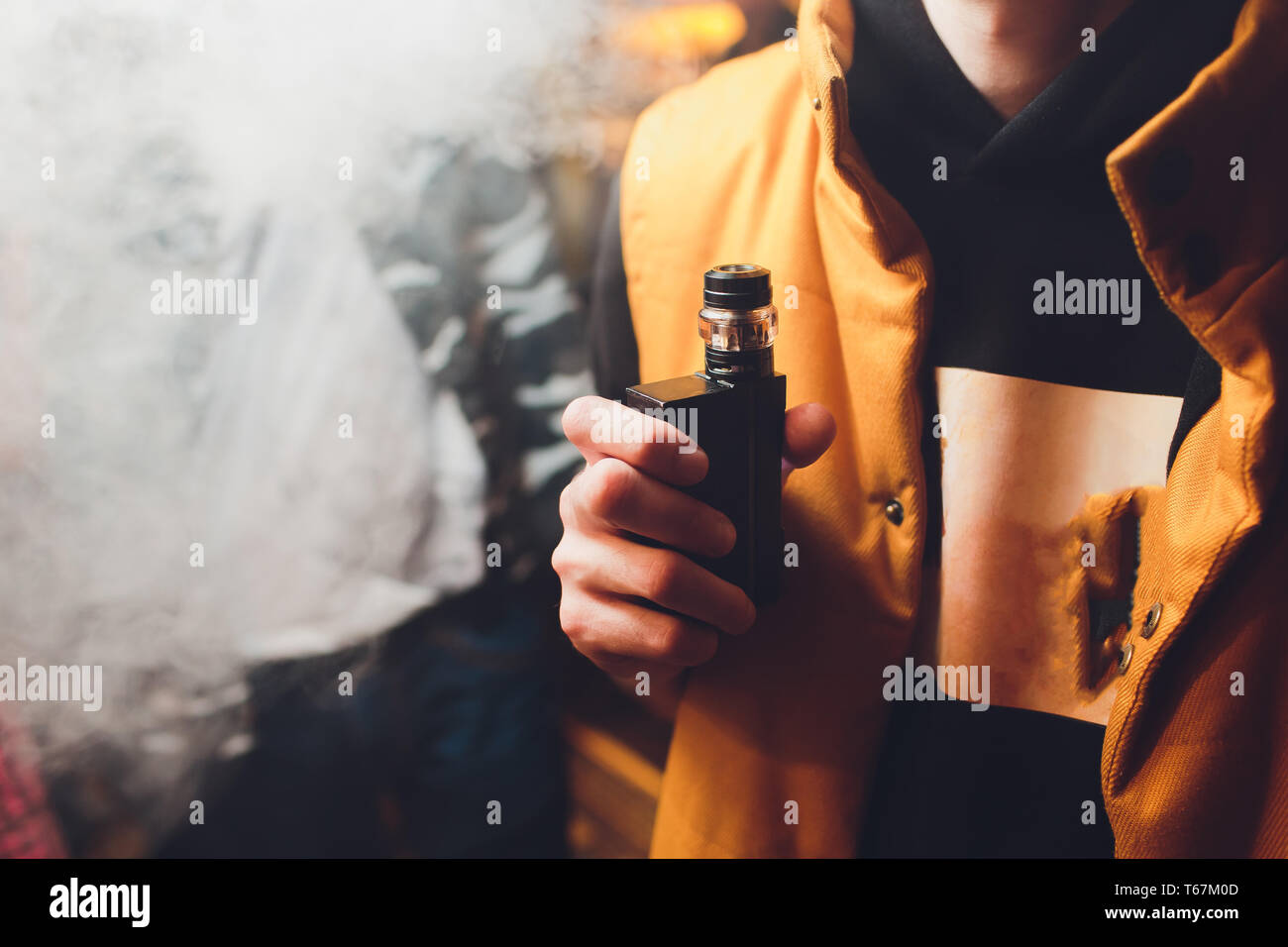 Man is smoking electronic cigarette or vaporizer. - Stock Image