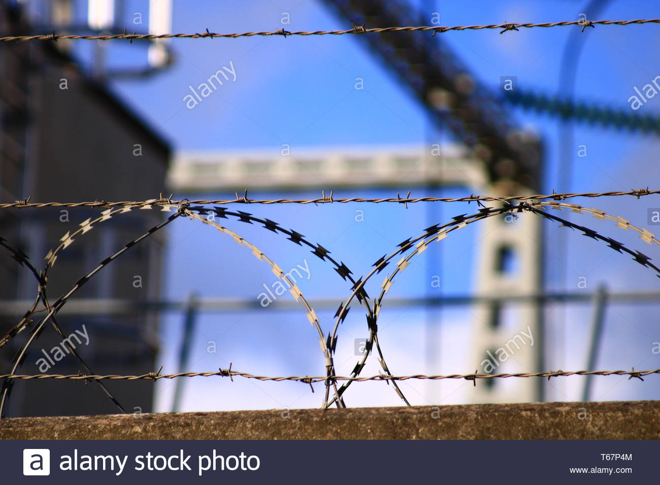 Anti intrusion system at the entrance of an industry View of barbed wire overhanging a perimeter wall - Stock Image