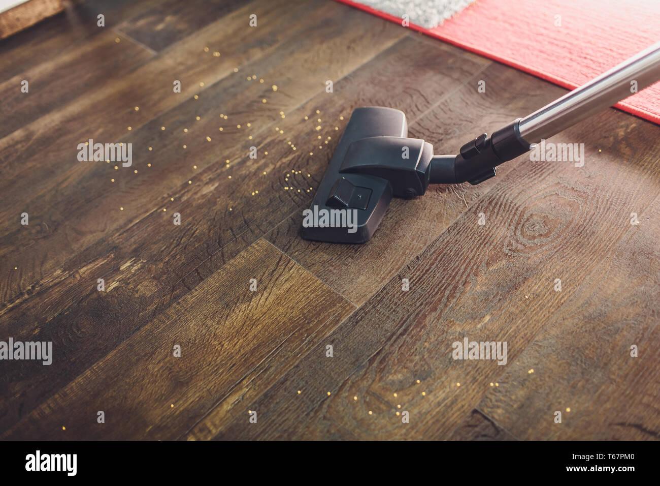 Dark head of a modern vacuum cleaner being used while