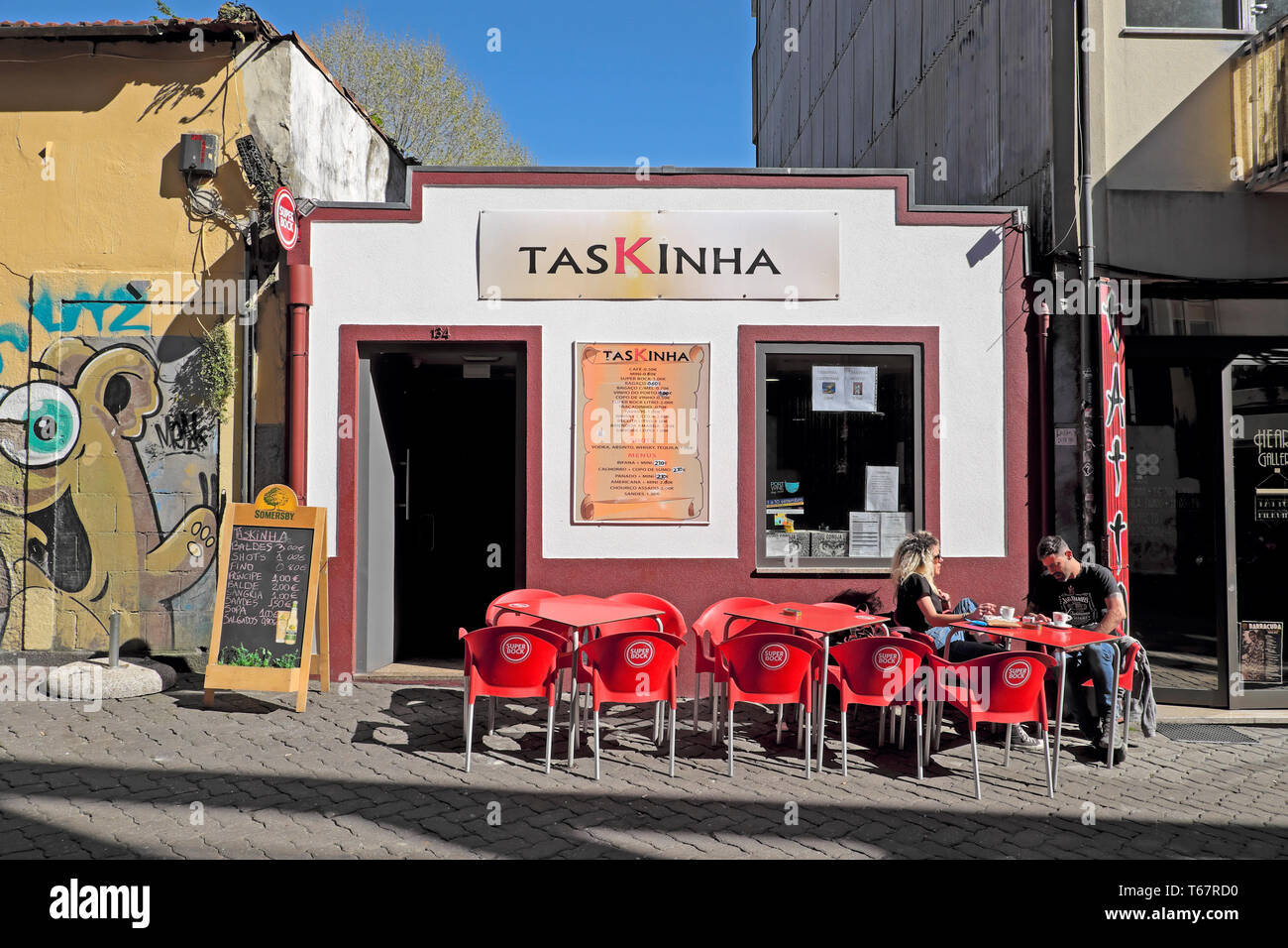 Exterior view of TasKinha bar and couple sitting outside at tables drinking in Porto, Oporto, Portugal   KATHY DEWITT - Stock Image