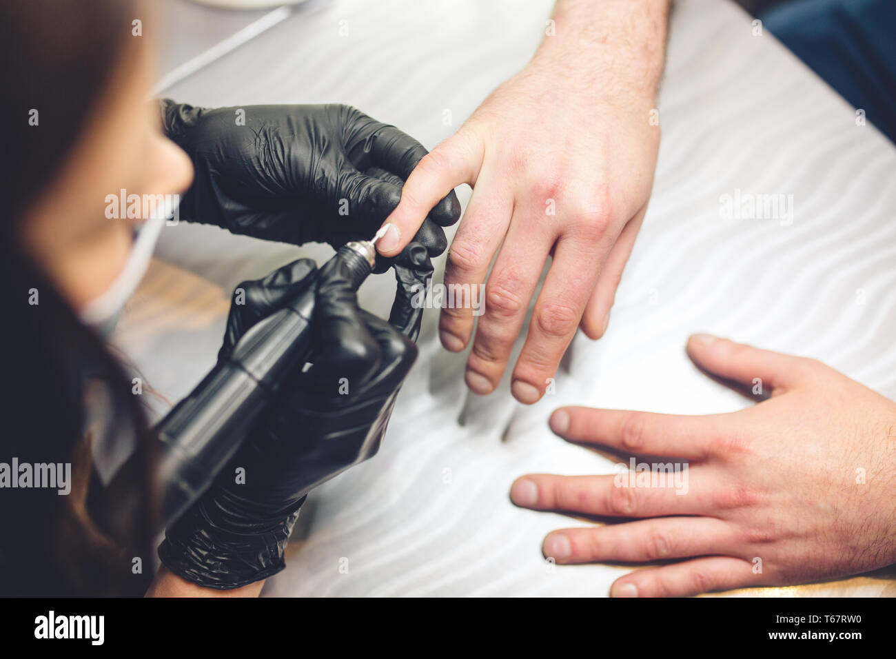 Men's manicure. Professional manicure for man by manicure machine. A man receiving a manicure in the beauty salon. Beautician master trimming and - Stock Image