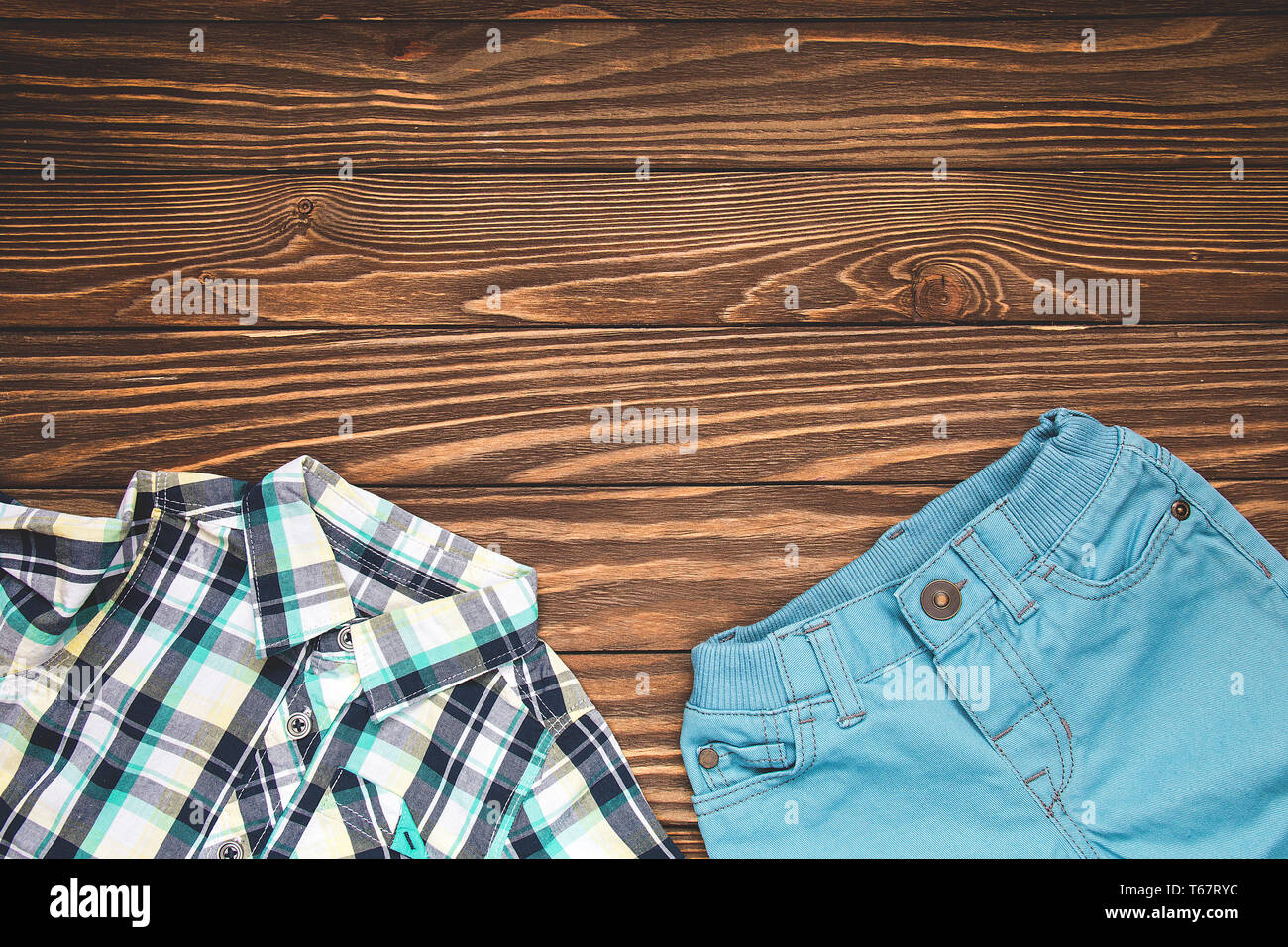 5ce5d98490714 Set of children's clothing for the boy. Blue pants and shirt on wooden  background.
