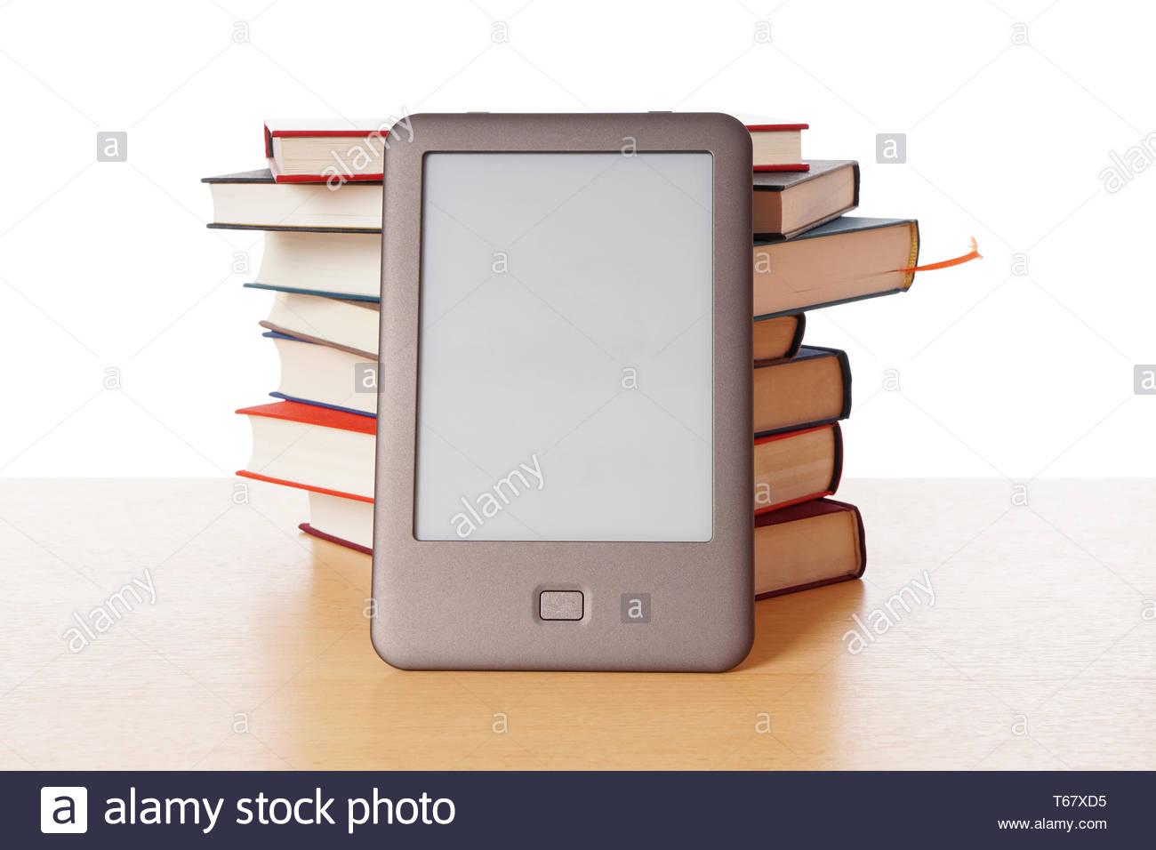 ebook reader vs pile of books - Stock Image
