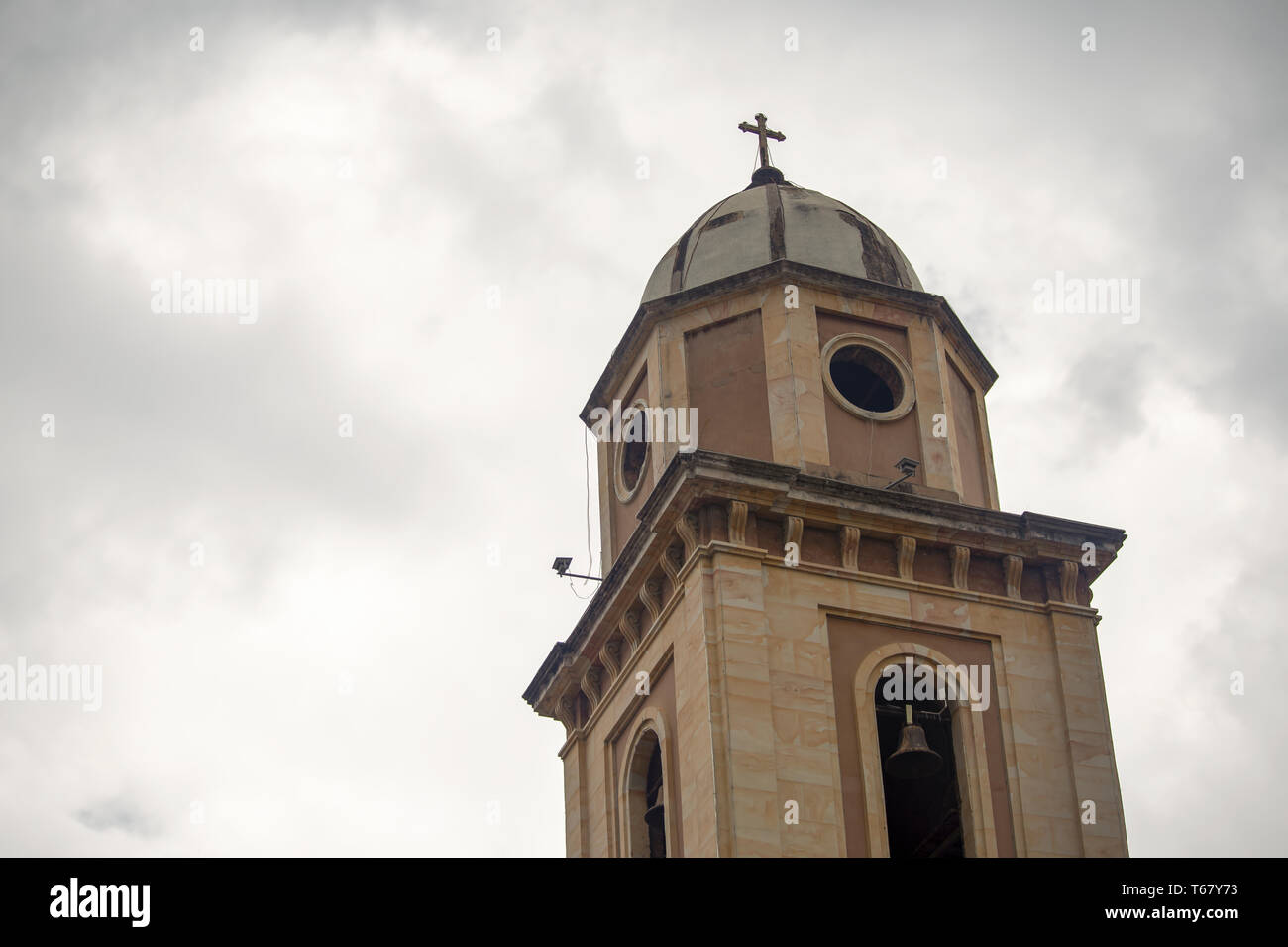 Bell tower of the colonial church of Iza, an old town in the Andean mountains of central Colombia, captured against the overcasted sky. Stock Photo