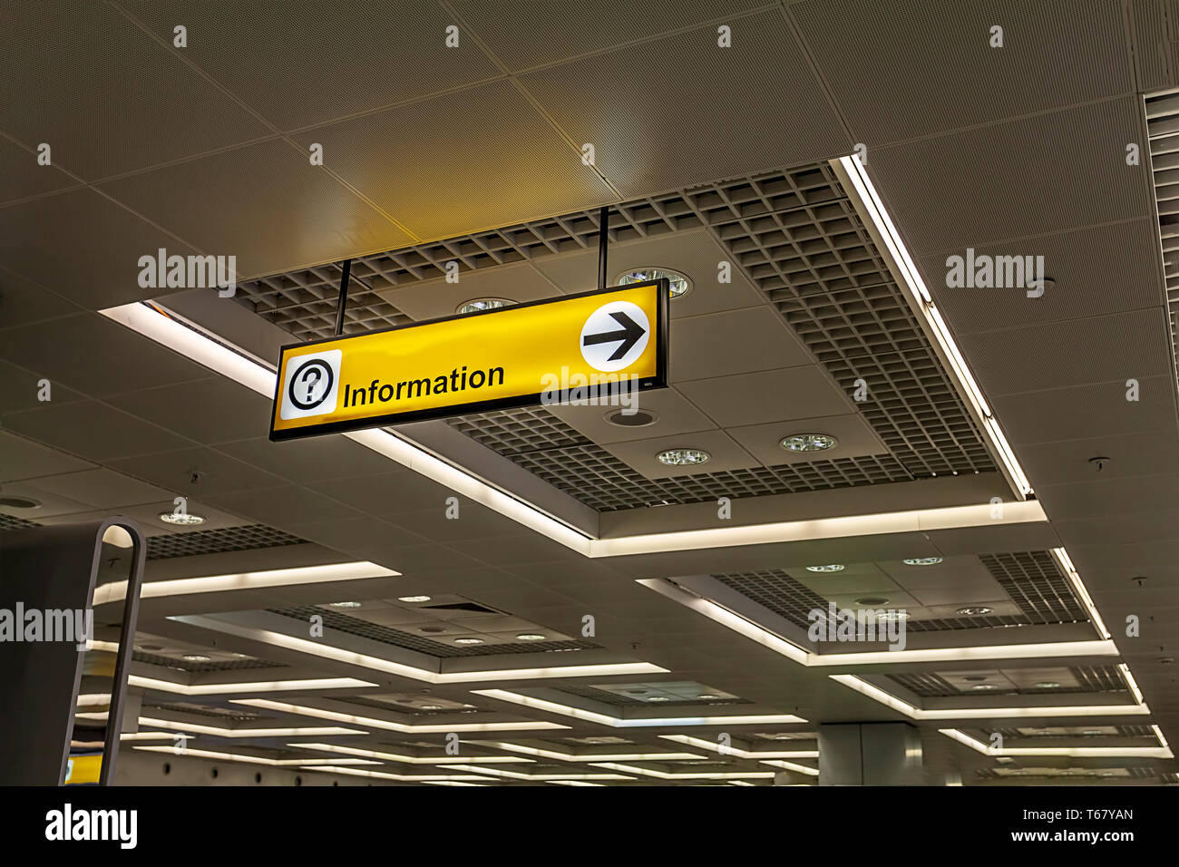 Indoor yellow bright invitation sign with question mark and road sign on airport and metro station - Stock Image