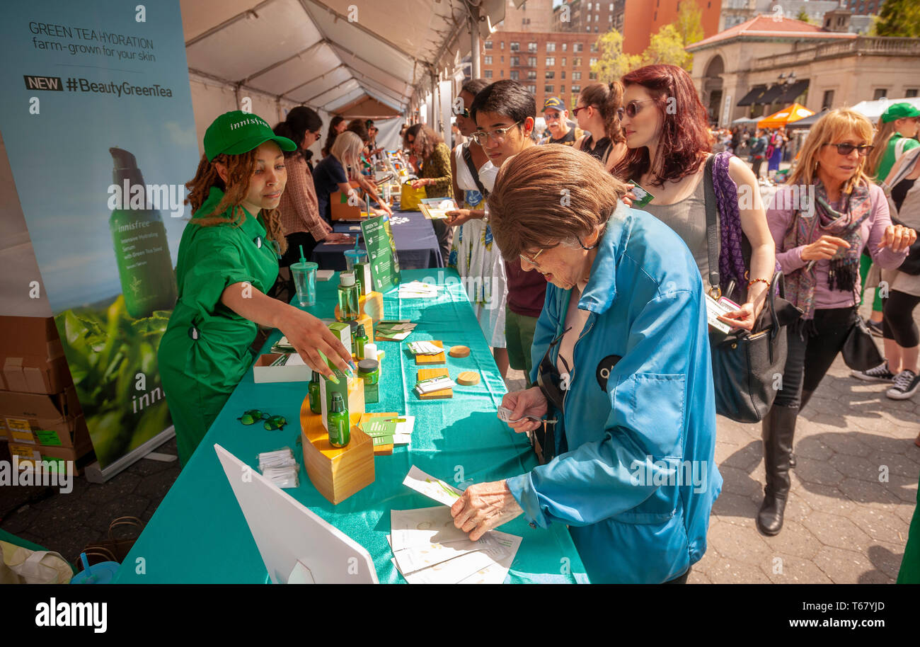 Workers for the Innisfree the Korean health and beauty product company, distribute samples of their Green Tea skin hydration formula at the Earth Day Street Fair in Union Square Park in New York on Tuesday, April 23, 2019. The fair featured booths from various companies and organizations touting their environmental awareness. (© Richard B. Levine) - Stock Image