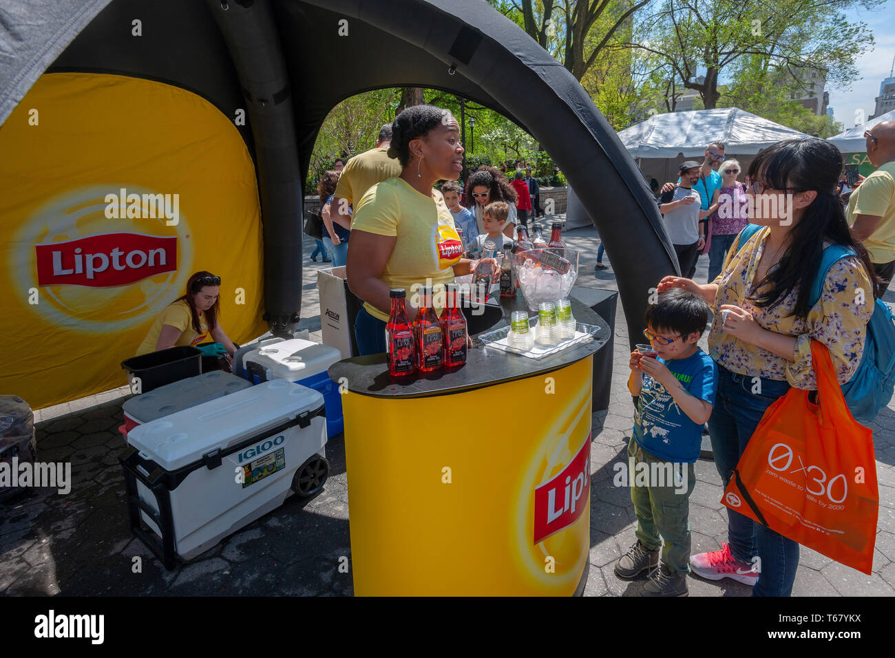Workers distribute samples of Unilever's Lipton Pure Leaf tea brand at the Earth Day Street Fair in Union Square Park in New York on Tuesday, April 23, 2019. The fair featured booths from various companies and organizations touting their environmental awareness. (© Richard B. Levine) - Stock Image
