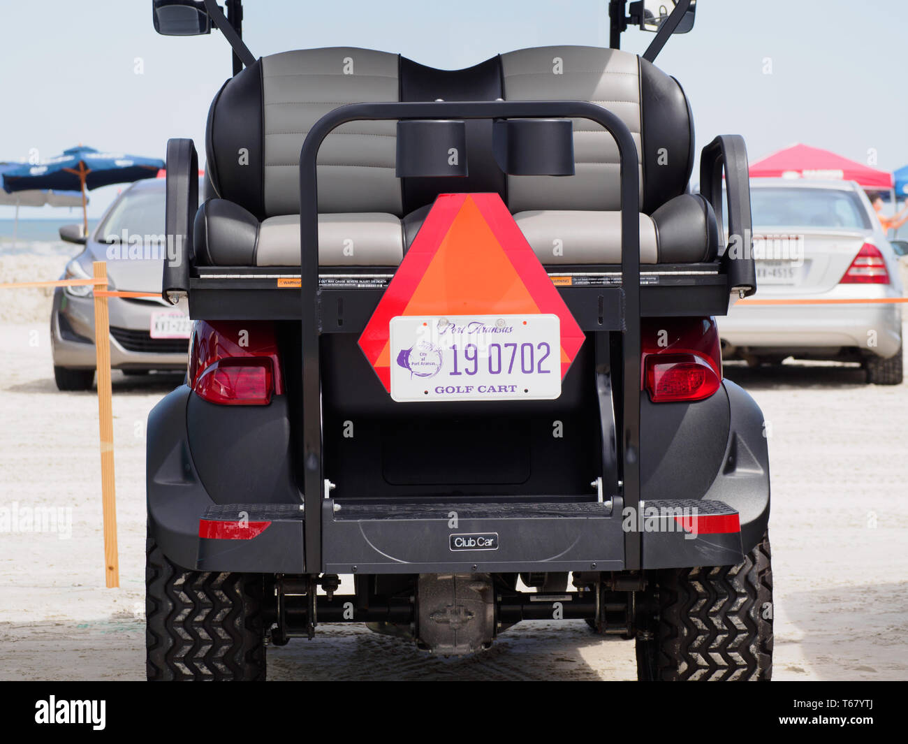 A golf cart with Port Aransas license plate sits in a beach parking lot at the 2019 Texas Sandfest in Port Aransas, Texas USA. - Stock Image