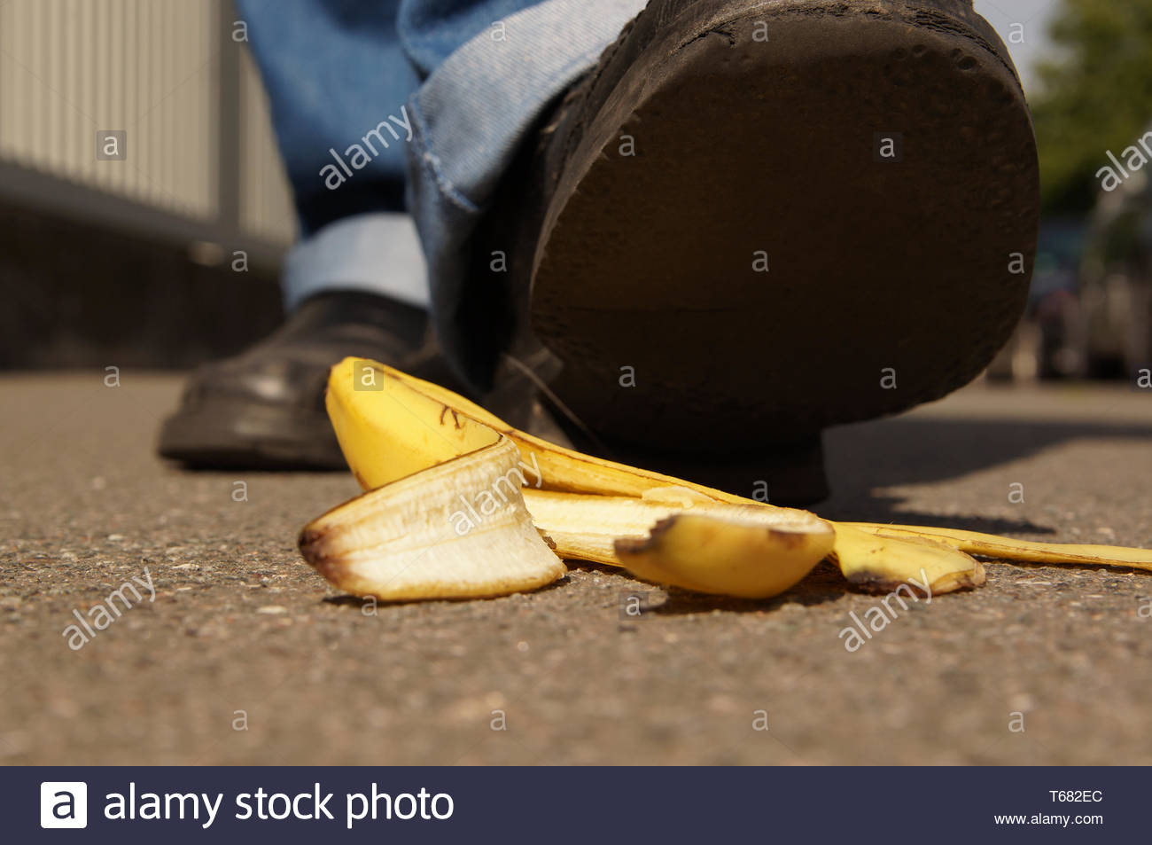slipping on a banana peel - Stock Image