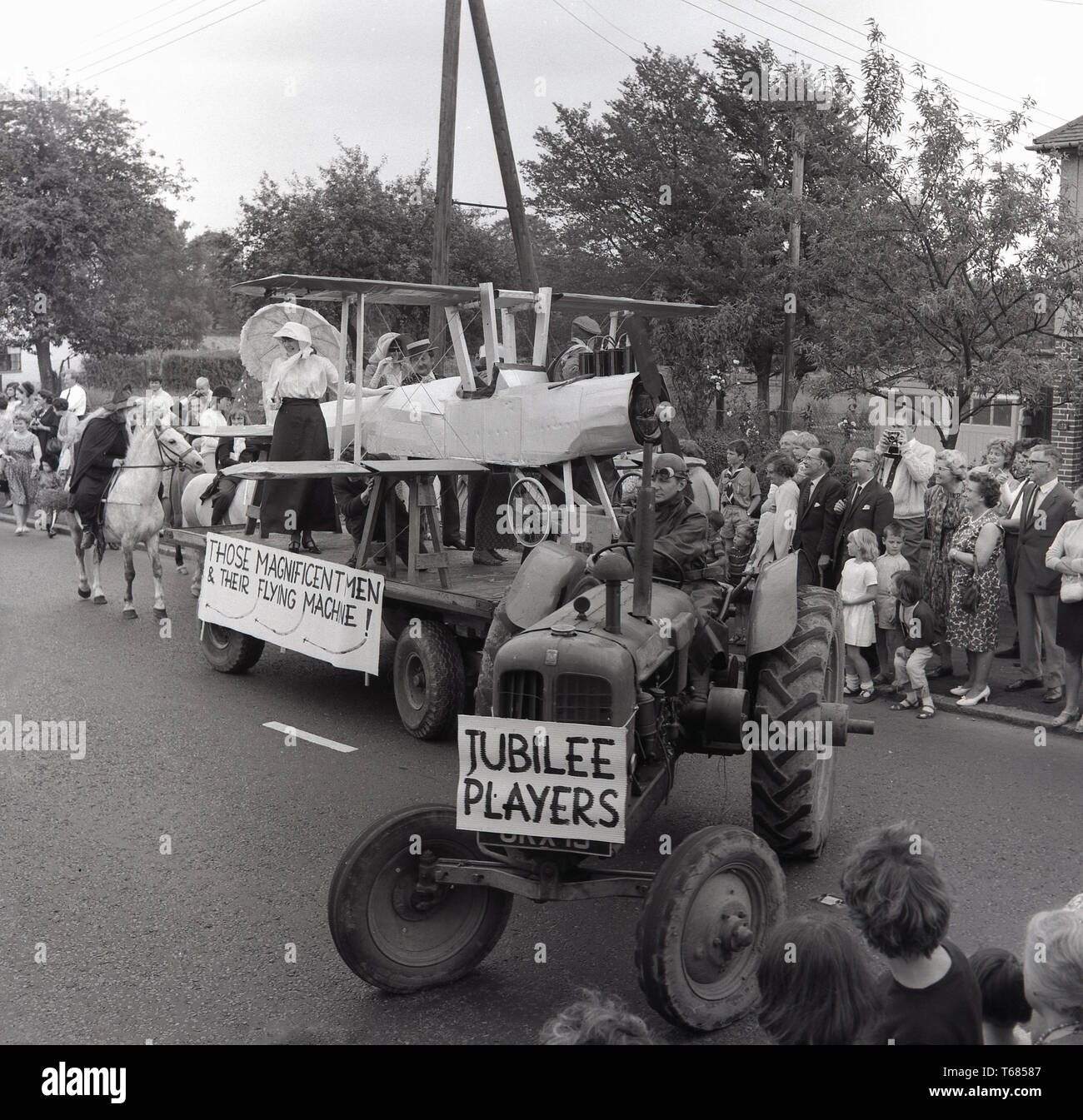 1960s, historical, spectators watch the local village carnival parade go pass, with a tractor pulling a float with a hand-made cardboard bi-plane on, followed by a witch on a horse, Prestwood, Bucks, England, UK. - Stock Image