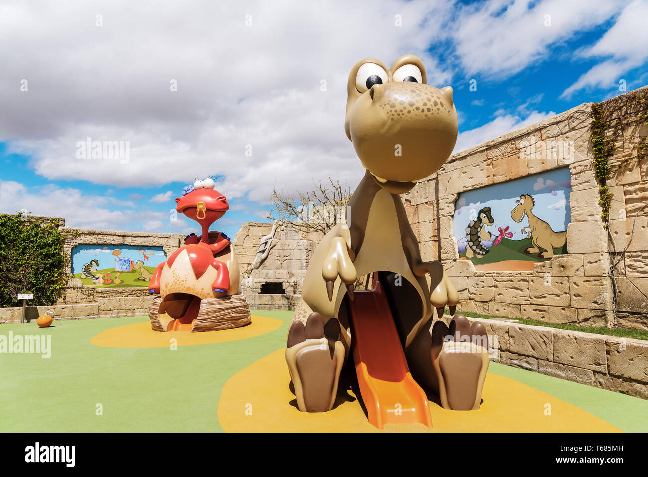 Children's playground with slides in the shape of cute dinosaurs. - Stock Image