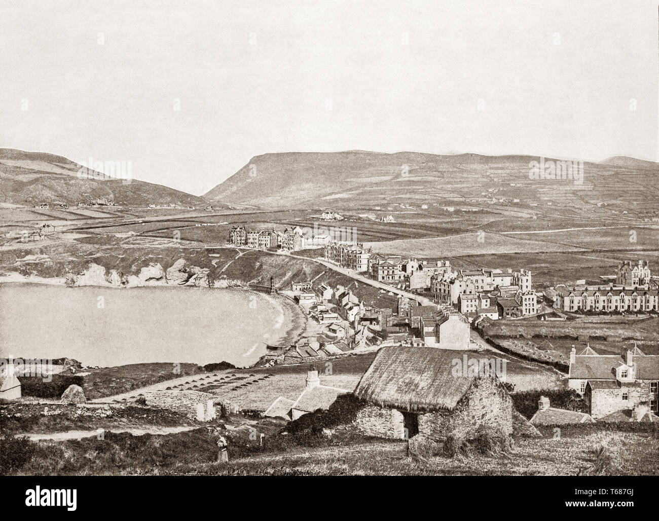 A 19th Century view of a traditional thatched cottage and farming just outside Port Erin, a seaside village in the south-west of the Isle of Man, a self-governing British Crown dependency in the Irish Sea between Great Britain and Ireland. - Stock Image