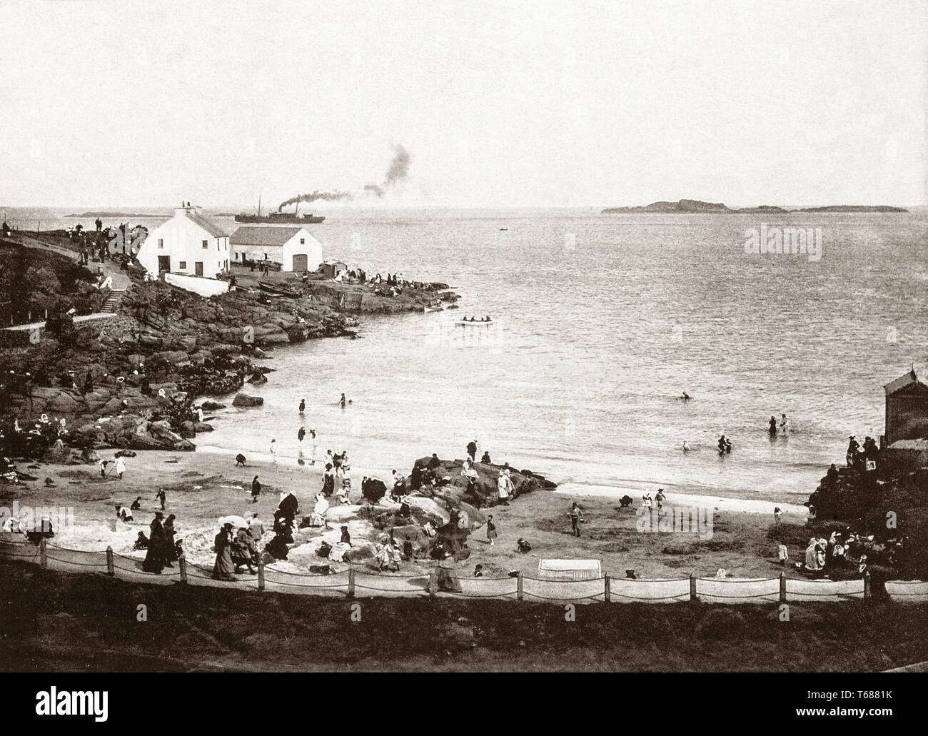 Late 19th Century view of the Bathing Place in Portrush, a small seaside resort town in County Antrim, Northern Ireland. Following the Wars of the Three Kingdoms in the mid-17th century, Portrush grew heavily from a small fishing town in the 19th century as a tourist destination, following the opening of the Ballymena, Ballymoney, Coleraine and Portrush Junction Railway in 1855. - Stock Image