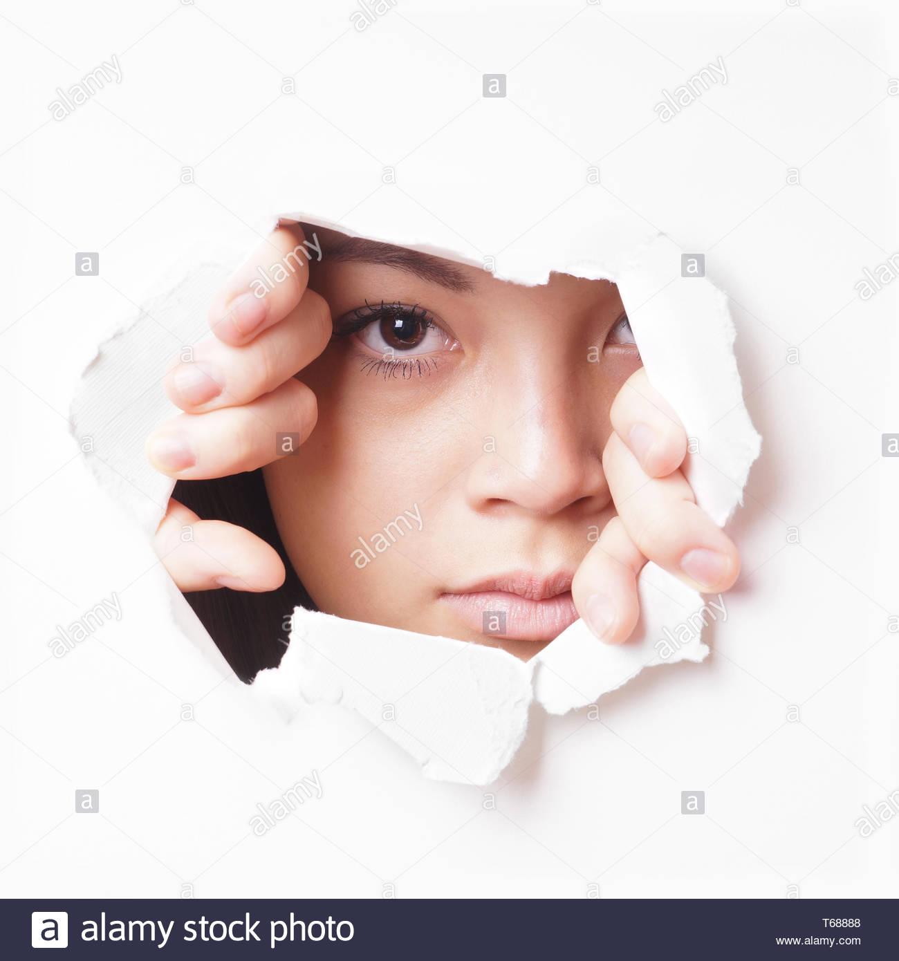 young asian woman peeking - Stock Image