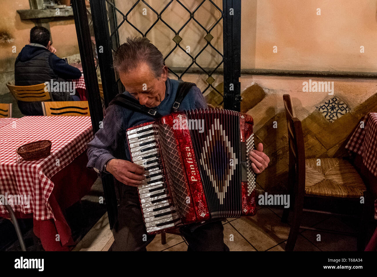 Playing music with an accordion for the tourists in a restaurant in Trastevere neighborhood - Stock Image