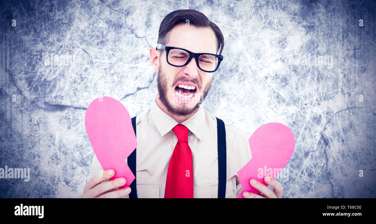 Composite image of geeky hipster crying and holding broken heart card - Stock Image
